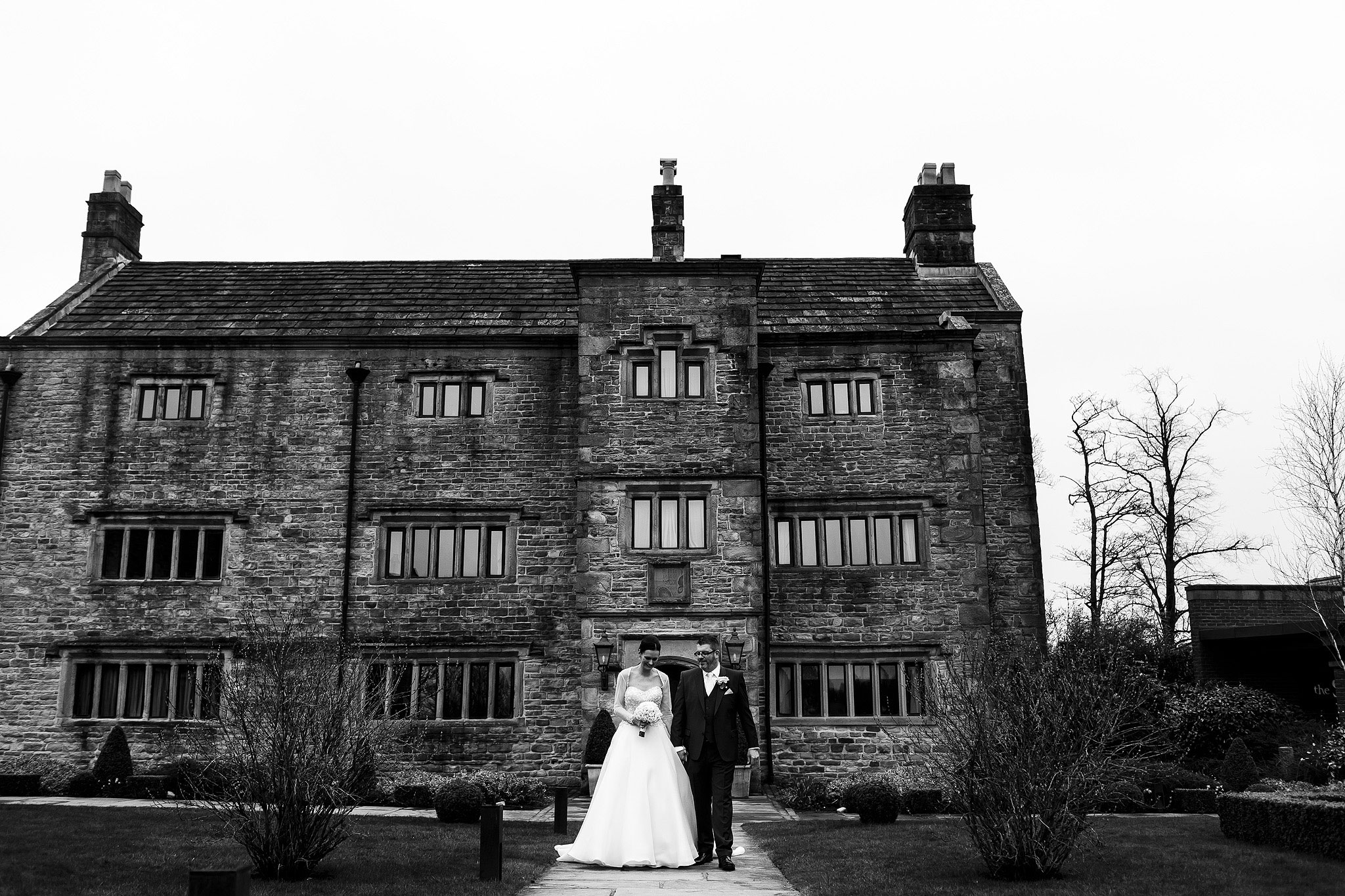 Bride and groom walking down the path way with Stanley House Hotel wedding venue in the background