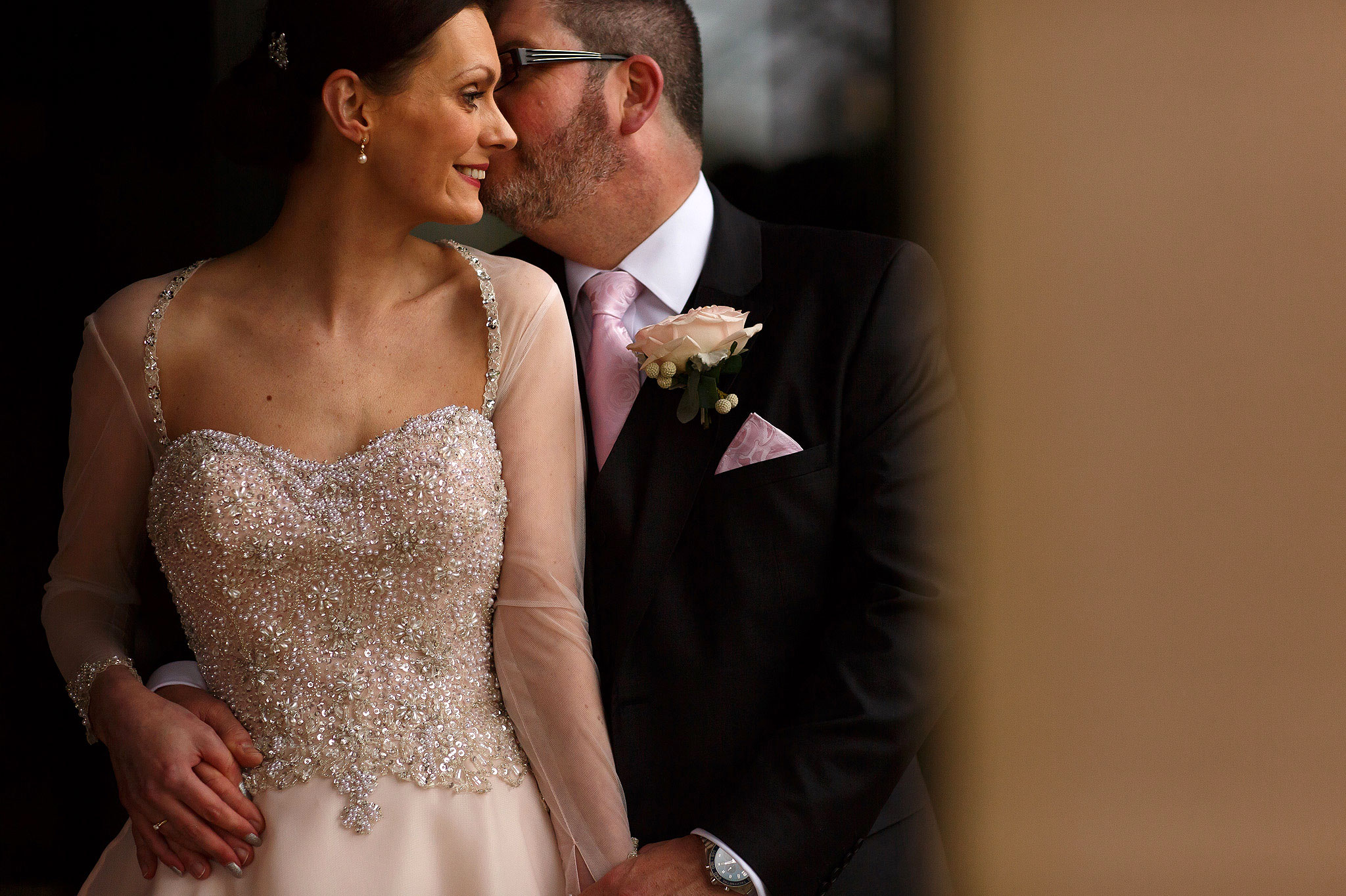 Bride wearing long sleeved pink wedding dress and groom with pink tie cuddling close during wedding portraits at Stanley House Hotel