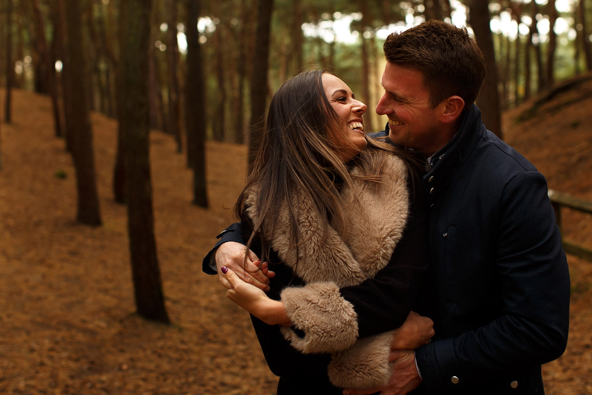 Brunette girl wearing fur coat on engagement shoot in the woods