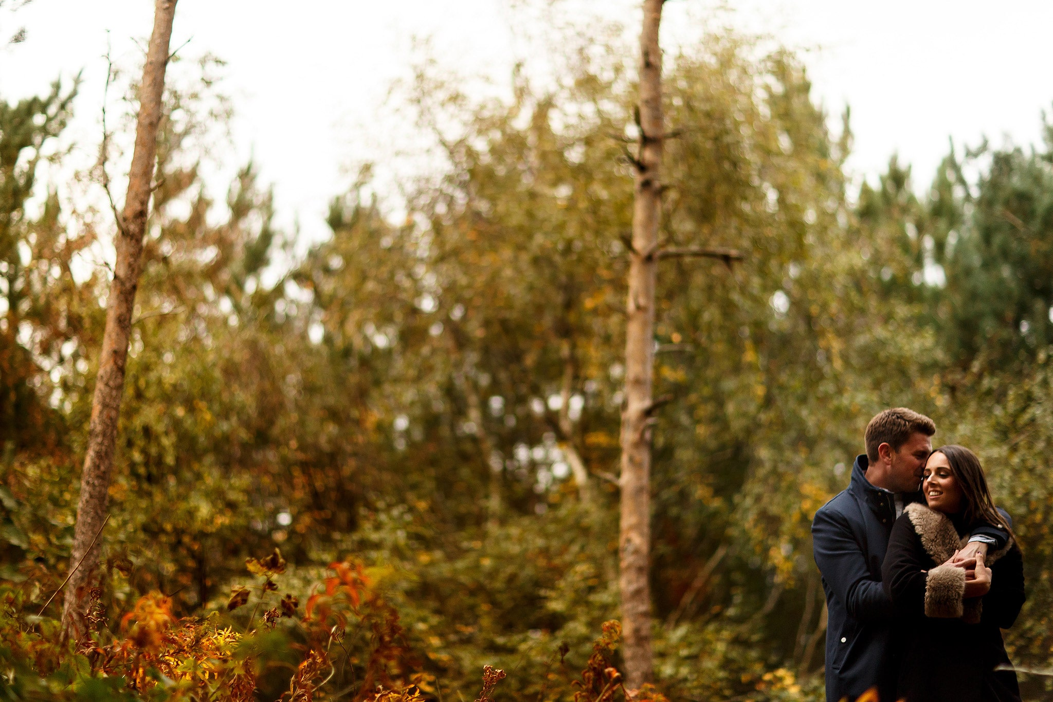 Girl laughing into the arms of boy at autumnal engagement shoot in the woods at formby point