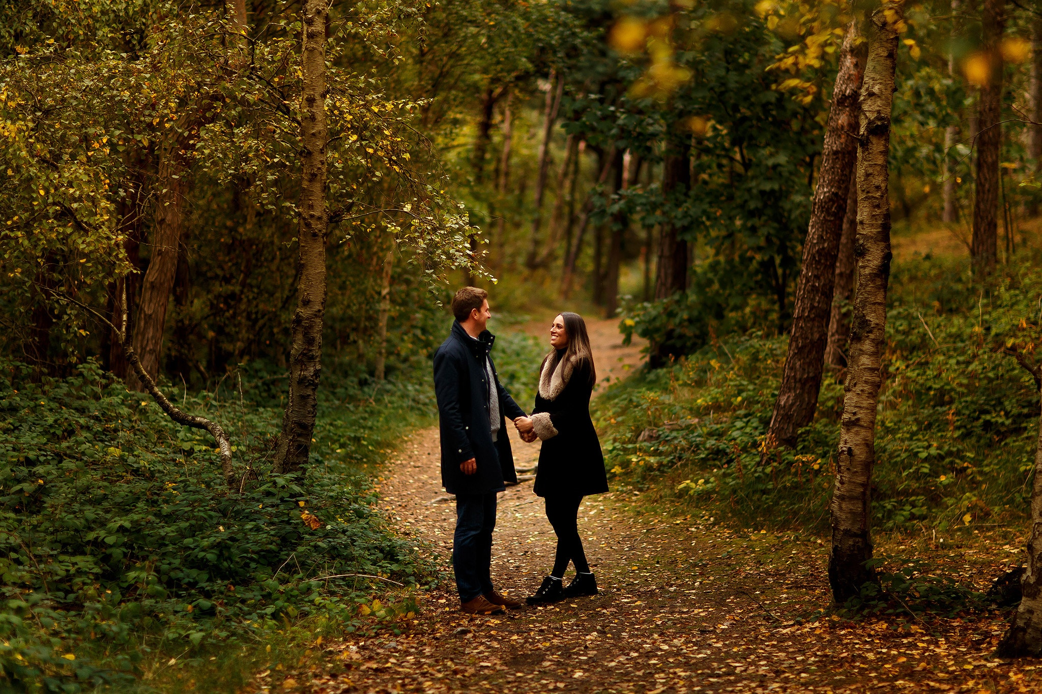 Girl laughing into the arms of boy as they walk down the path in the woods for autumnal engagement shoot in the woods at formby point