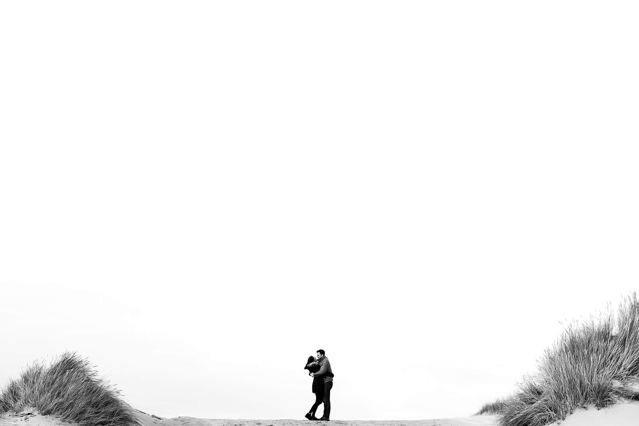 couple running in the sand dunes for engagement shoot at formby point