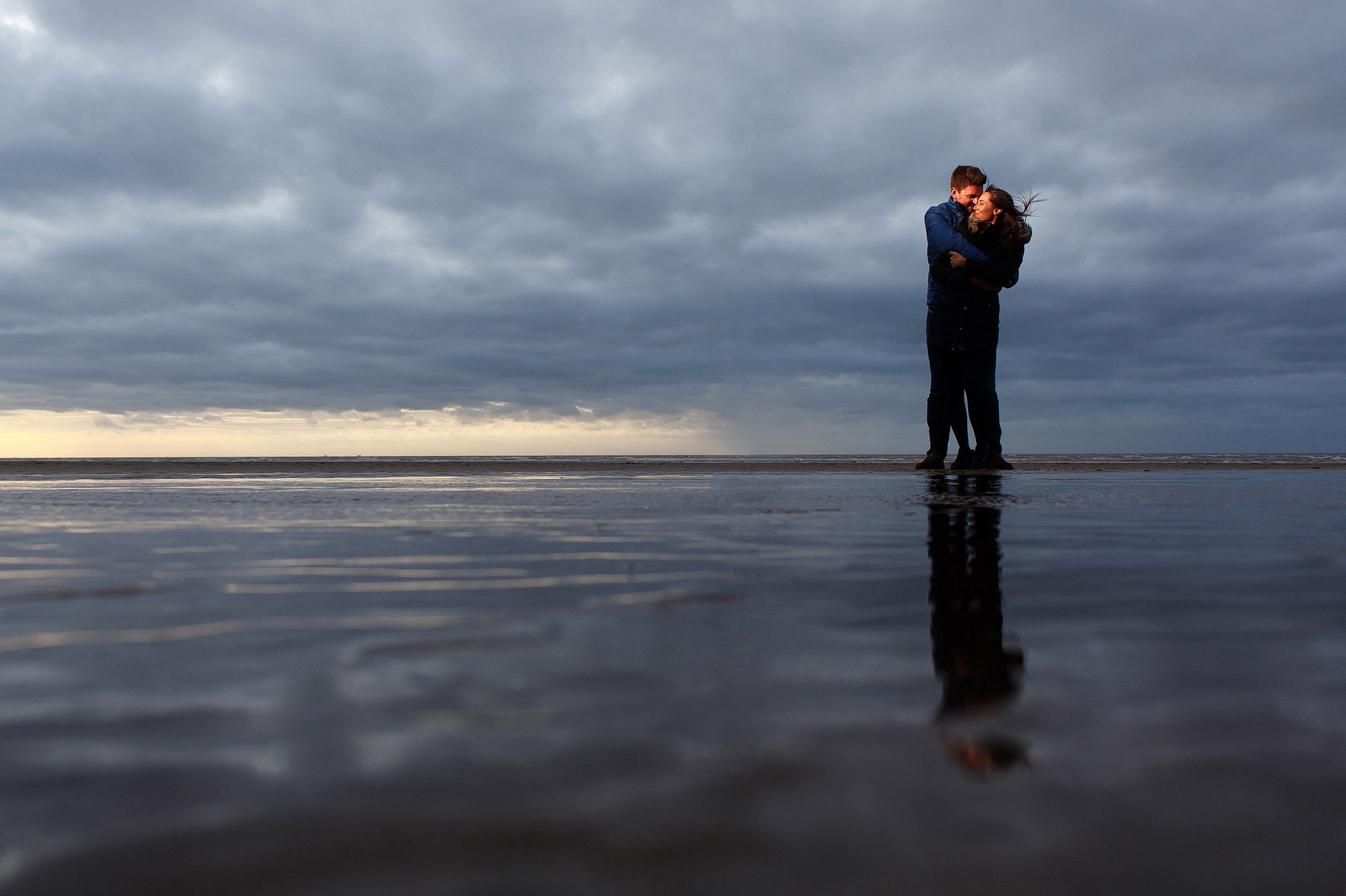 couple laughing in each others arms on the beach at sunset during engagement shoot