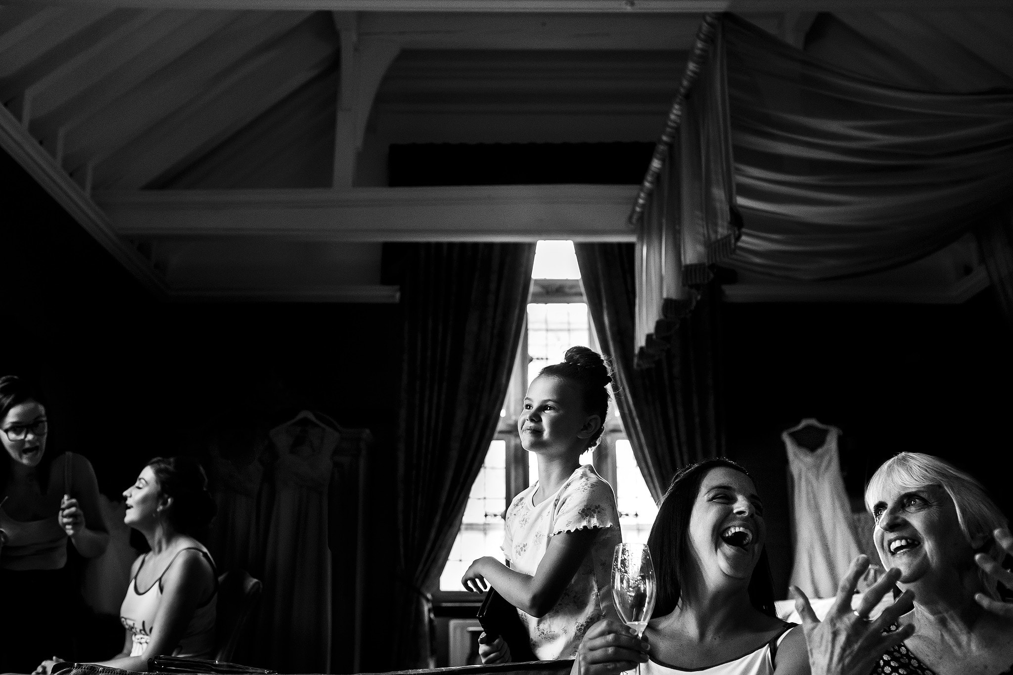 Black and white image of flower girl perfectly framed with wedding dress hanging in the background