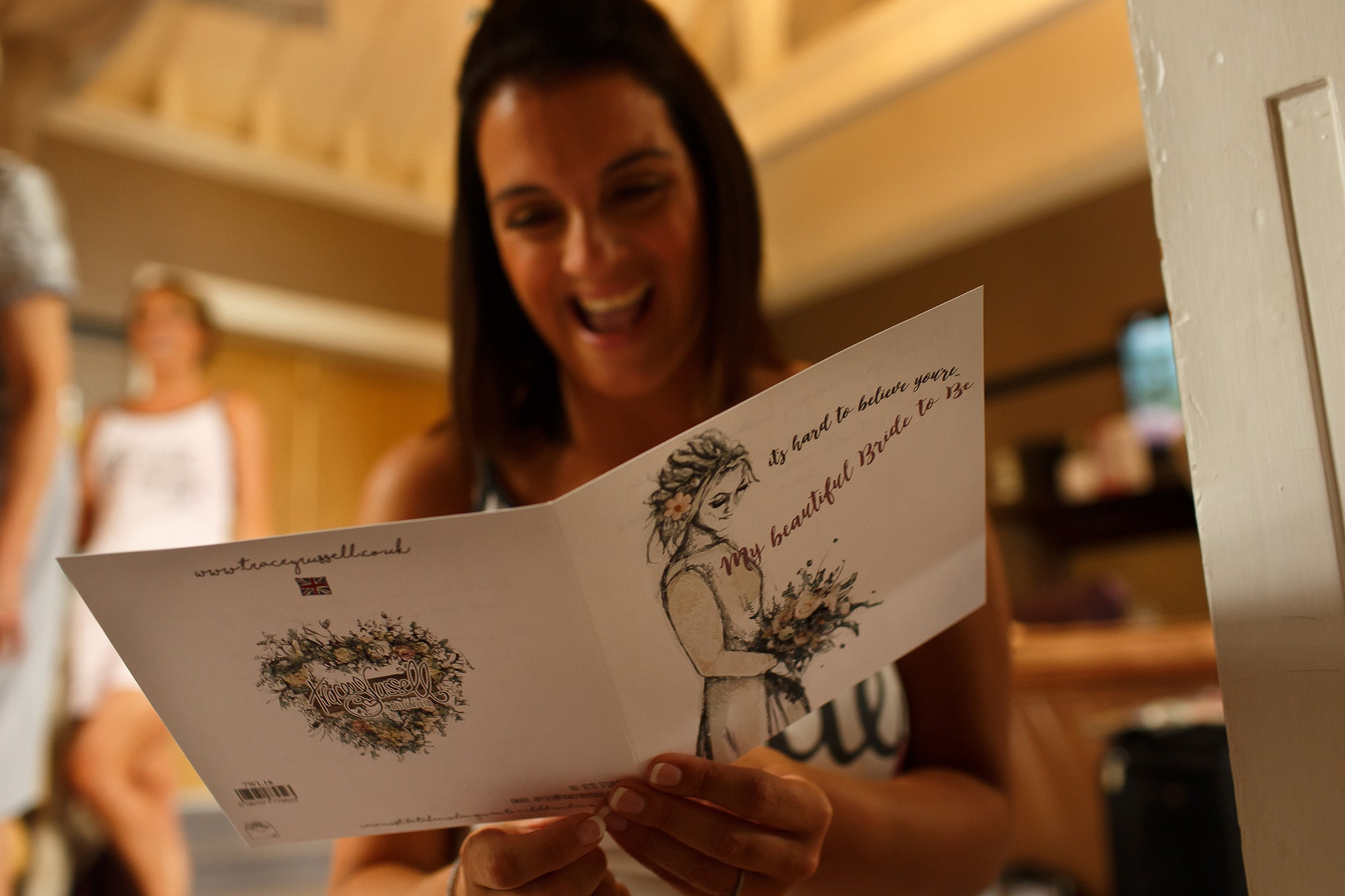 Bride laughing at wedding card from the groom