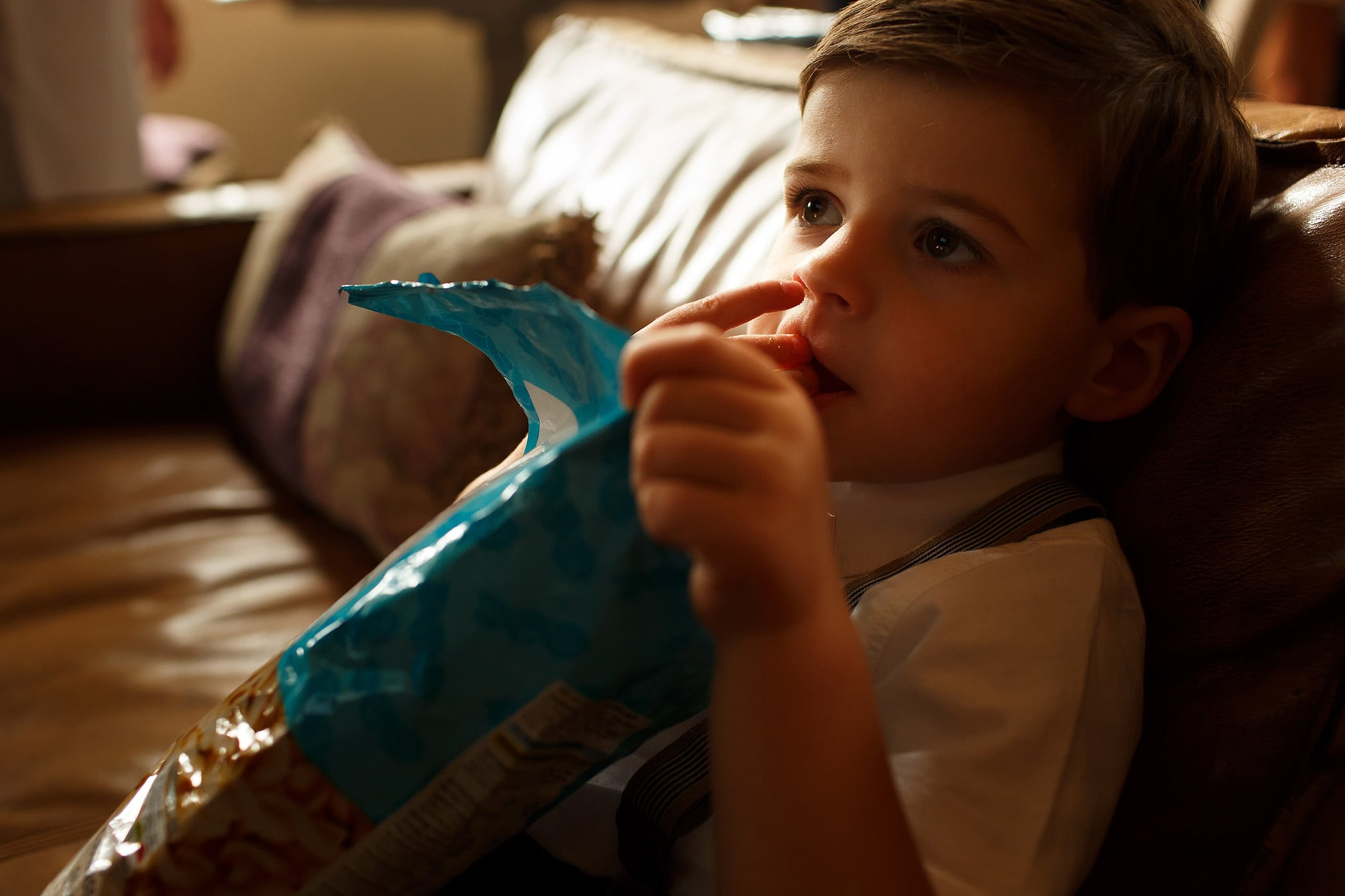 Pay boy eating family size bag of crisps at wedding