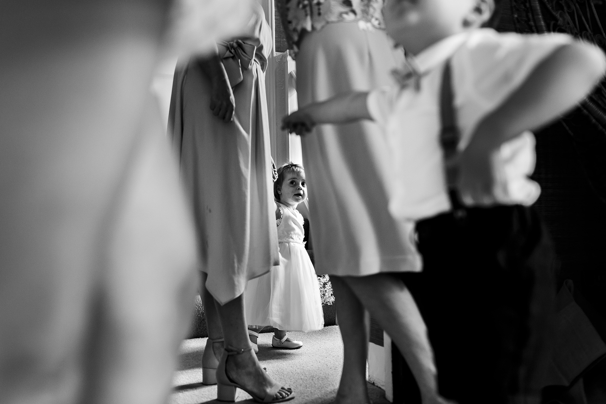 Flower girl only visible in between all the legs of bridesmaids