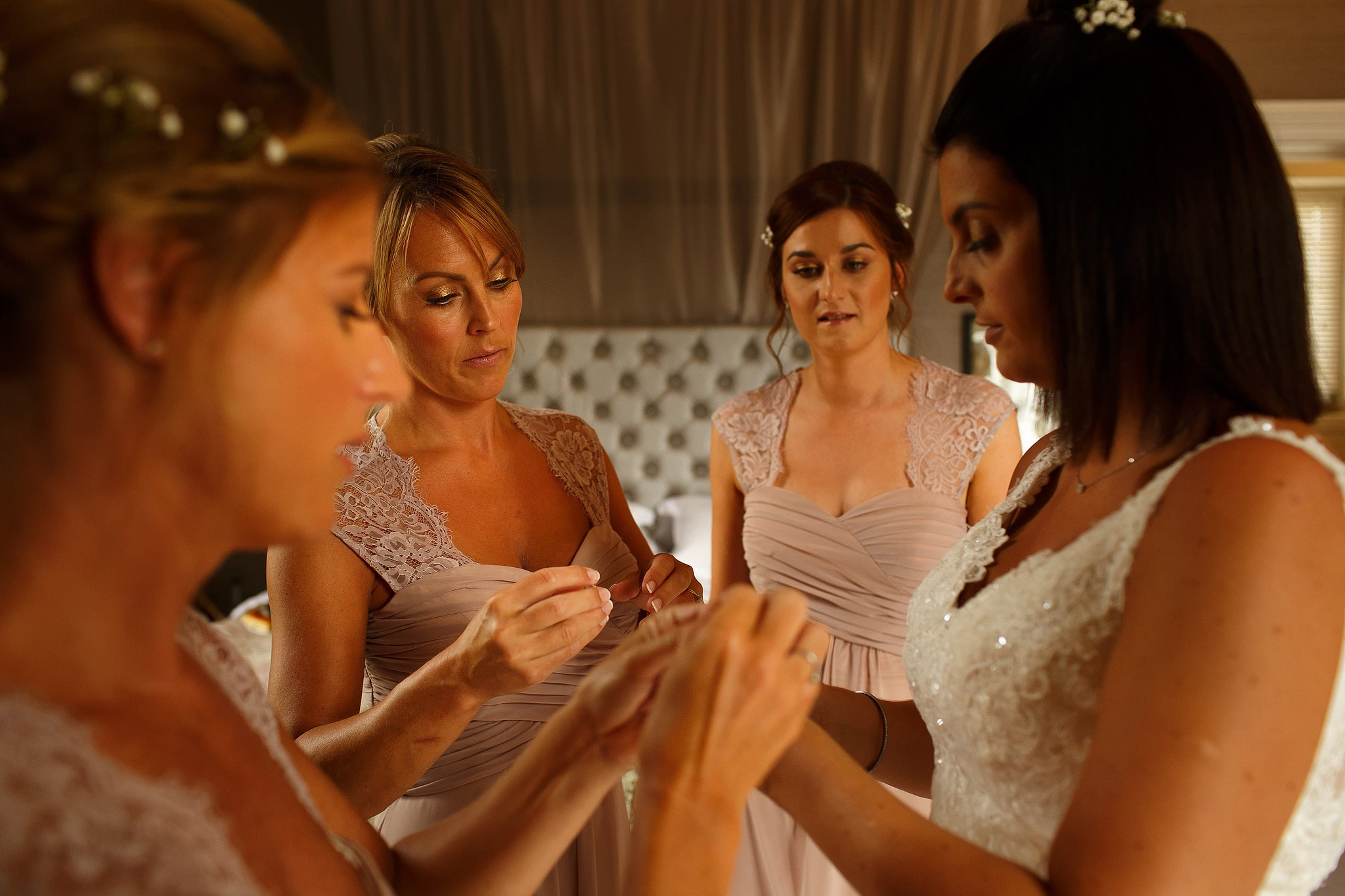 Bridesmaids wearing blush pink helping the bride into her wedding dress at Falcon Manor wedding