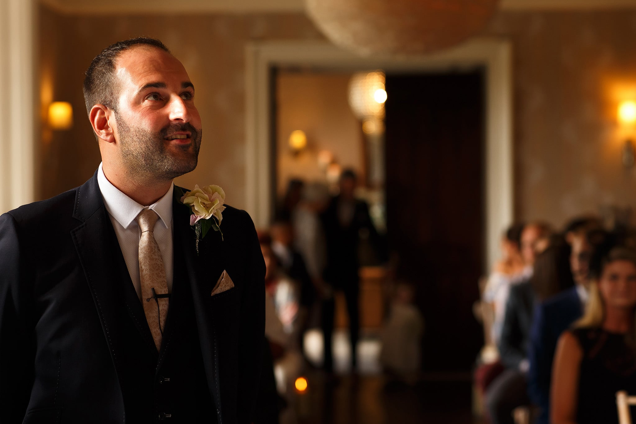 Nervous groom waiting at the top of the aisle in ceremony room at falcon manor