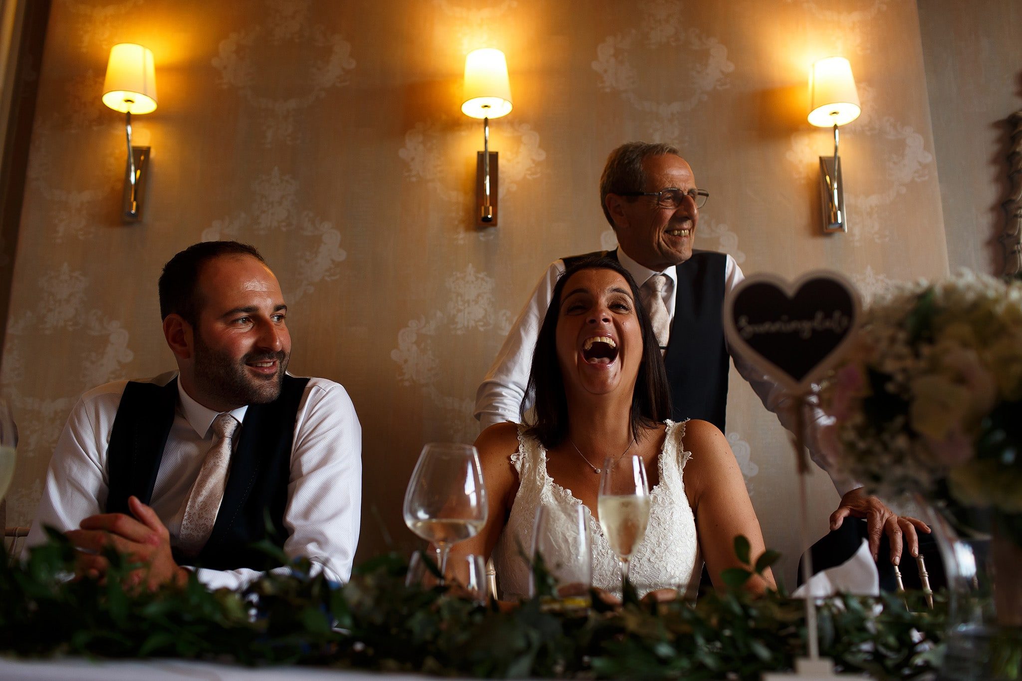 Bride laughing during wedding speeches at Falcon Manor reception
