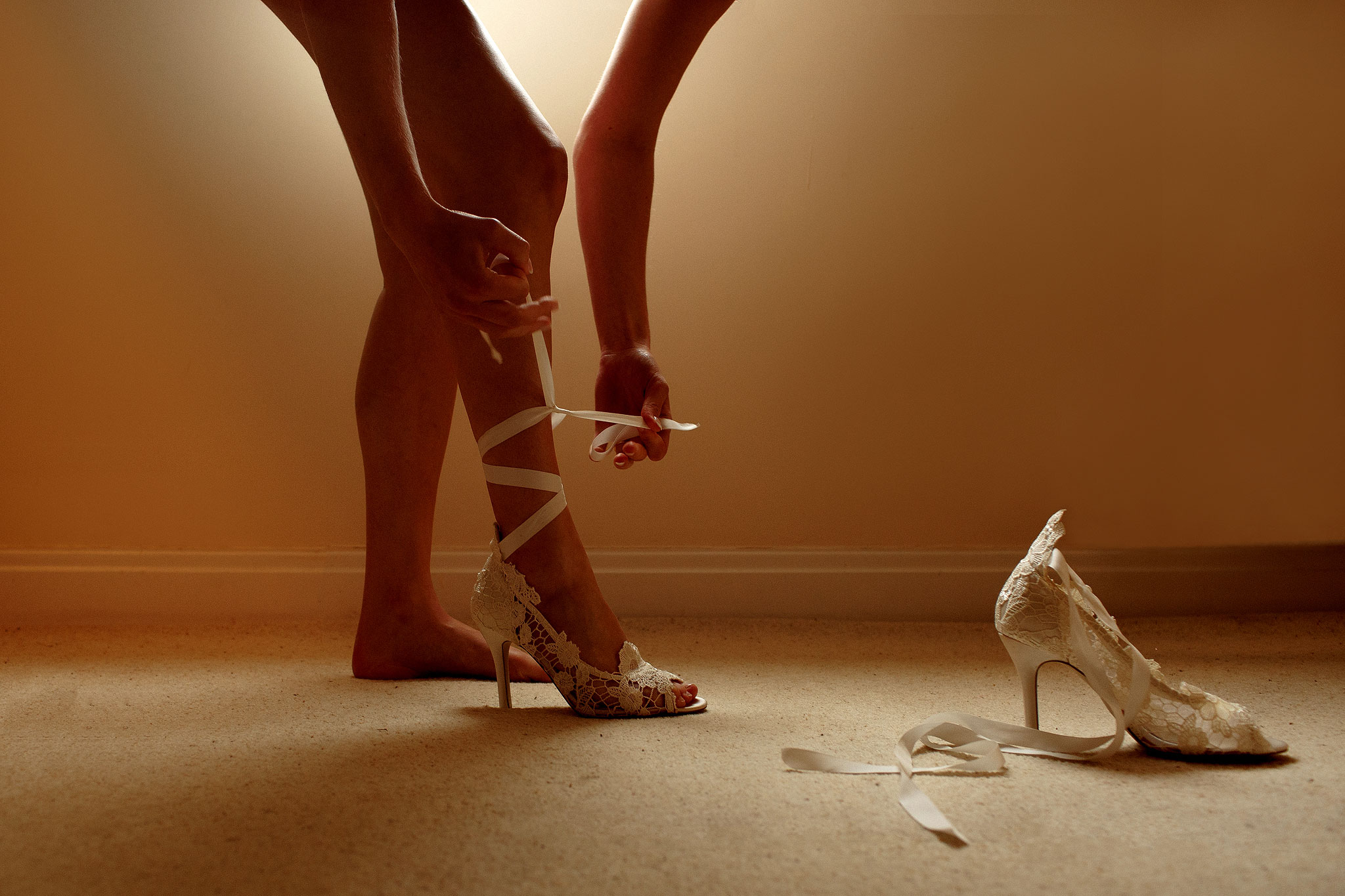 Legs of bride as she ties high heel cream shoes with ribbon ties that wrap around the leg
