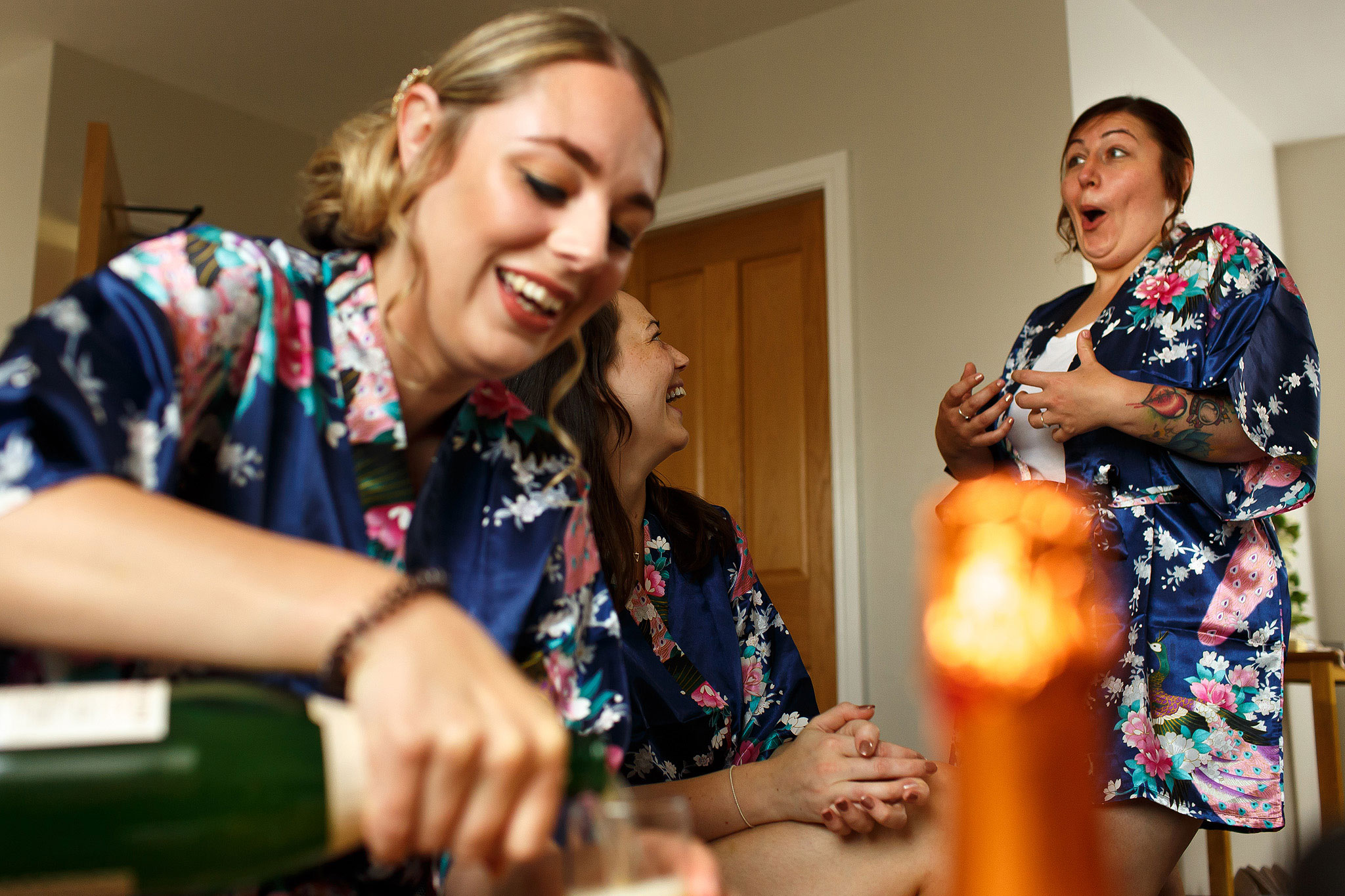 Bridesmaids pouring champagne wearing matching floral silk gowns - The Villa at Wrea Green Wedding Photography - Toni Darcy Photography