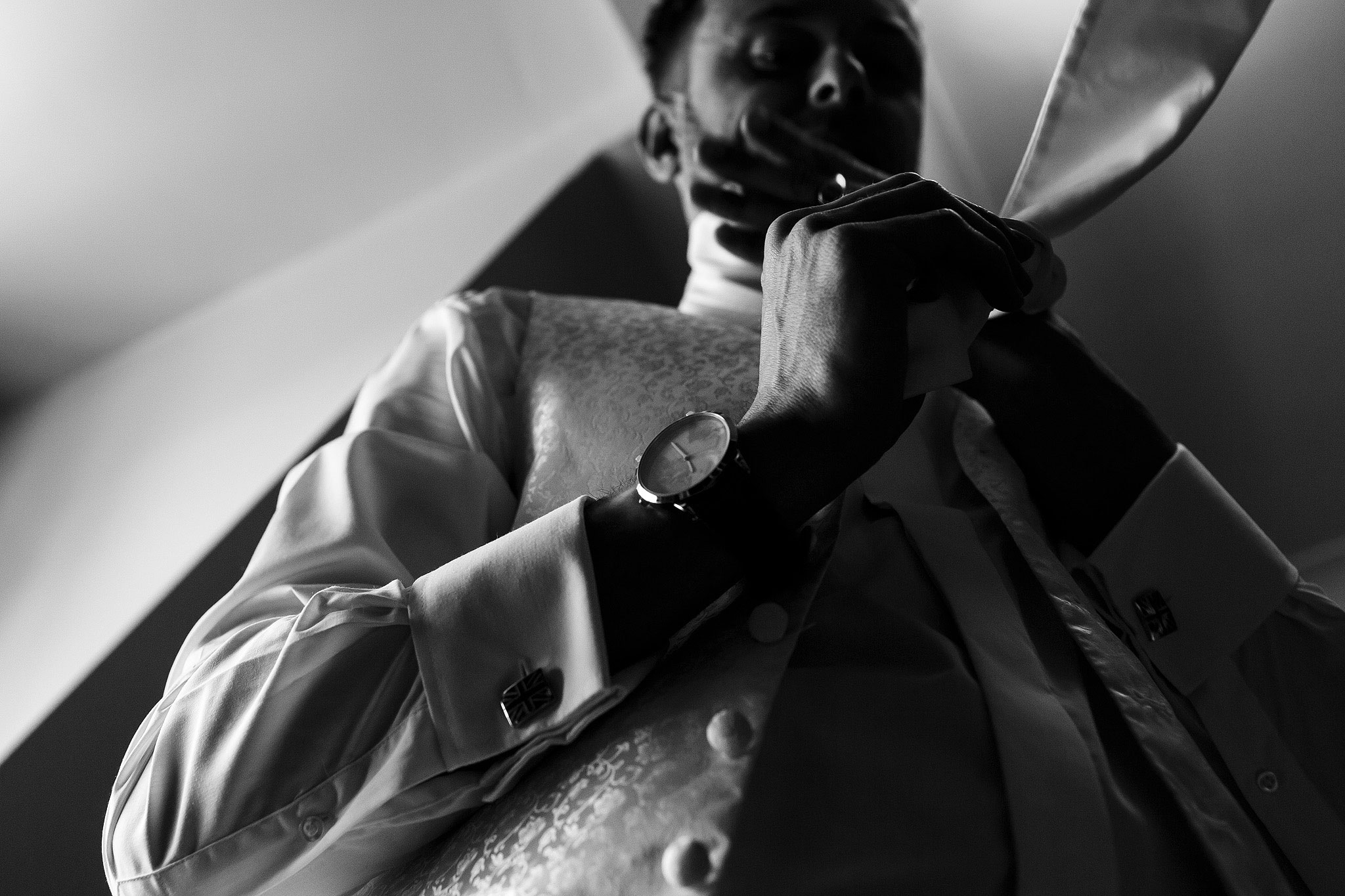Groom fastening tie on morning of wedding day. Taken from a creative perspective - The Villa at Wrea Green Wedding Photography - Toni Darcy Photography