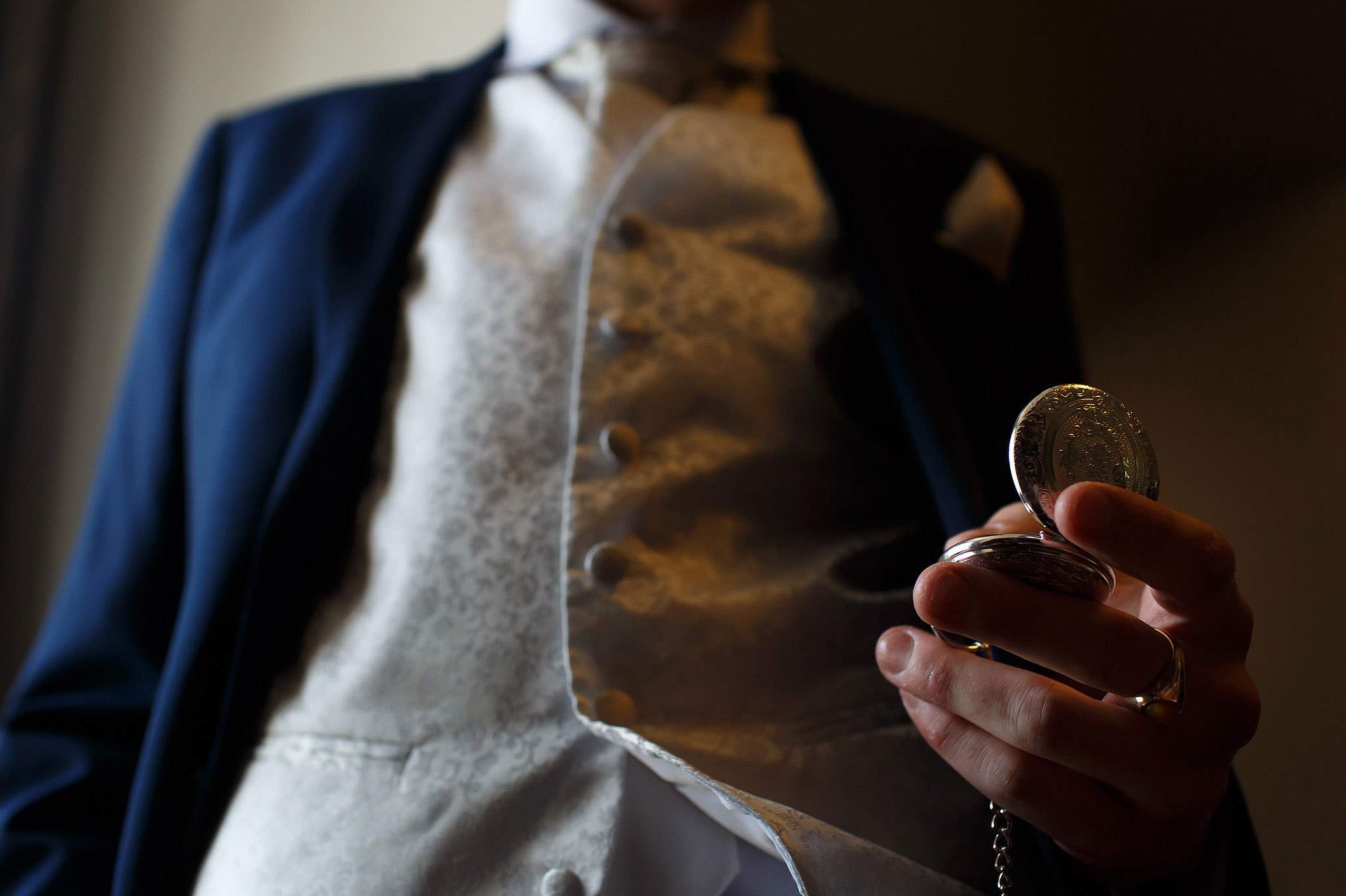 Groom wearing blue suit and cream waist coat holding pocket watch on morning of wedding day - The Villa at Wrea Green Wedding Photography - Toni Darcy Photography