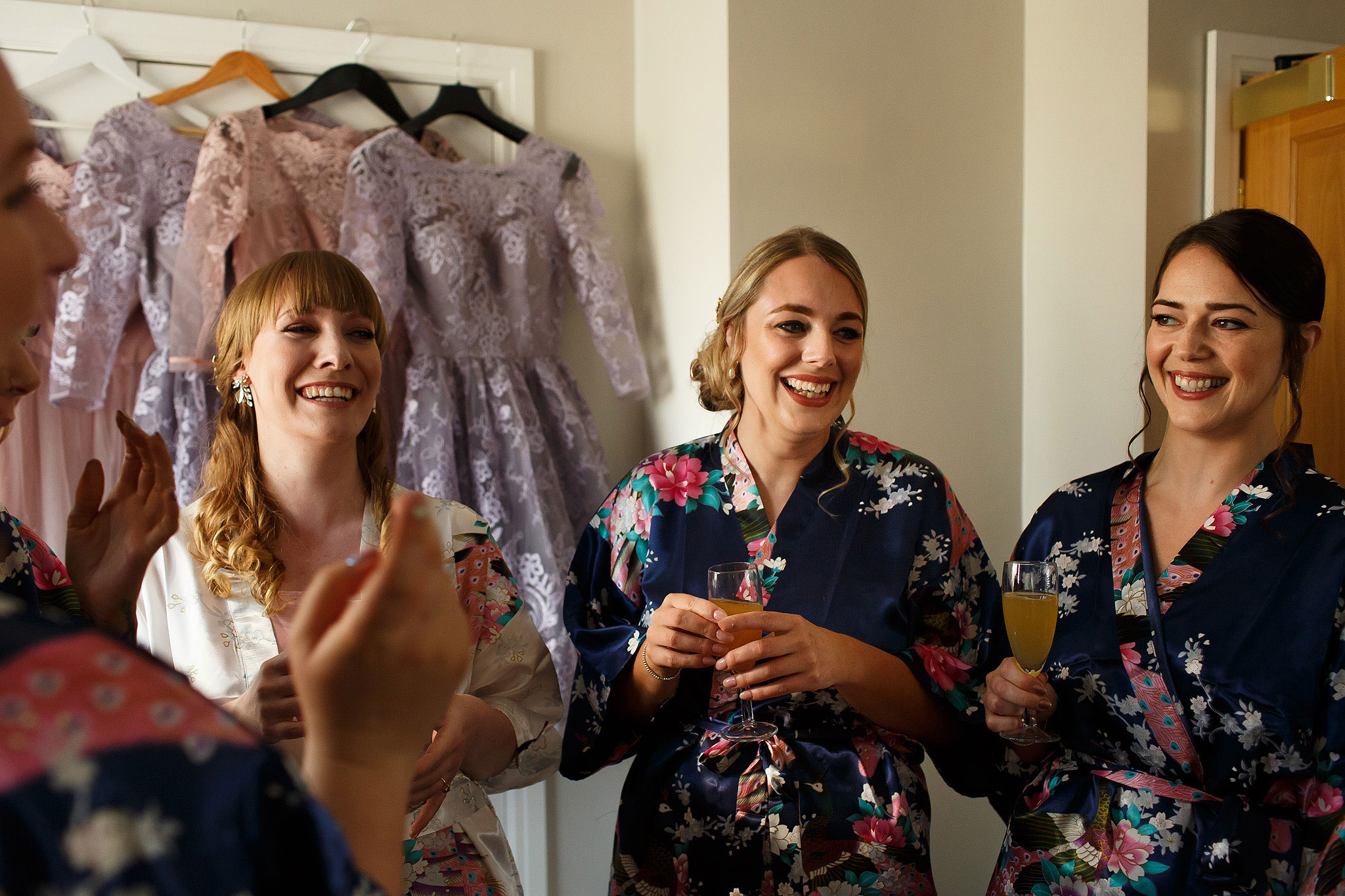Bride and bridesmaids laughing wearing matching silk wedding dresses holding champagne on morning of wedding in bridal suite - The Villa at Wrea Green Wedding Photography - Toni Darcy Photography