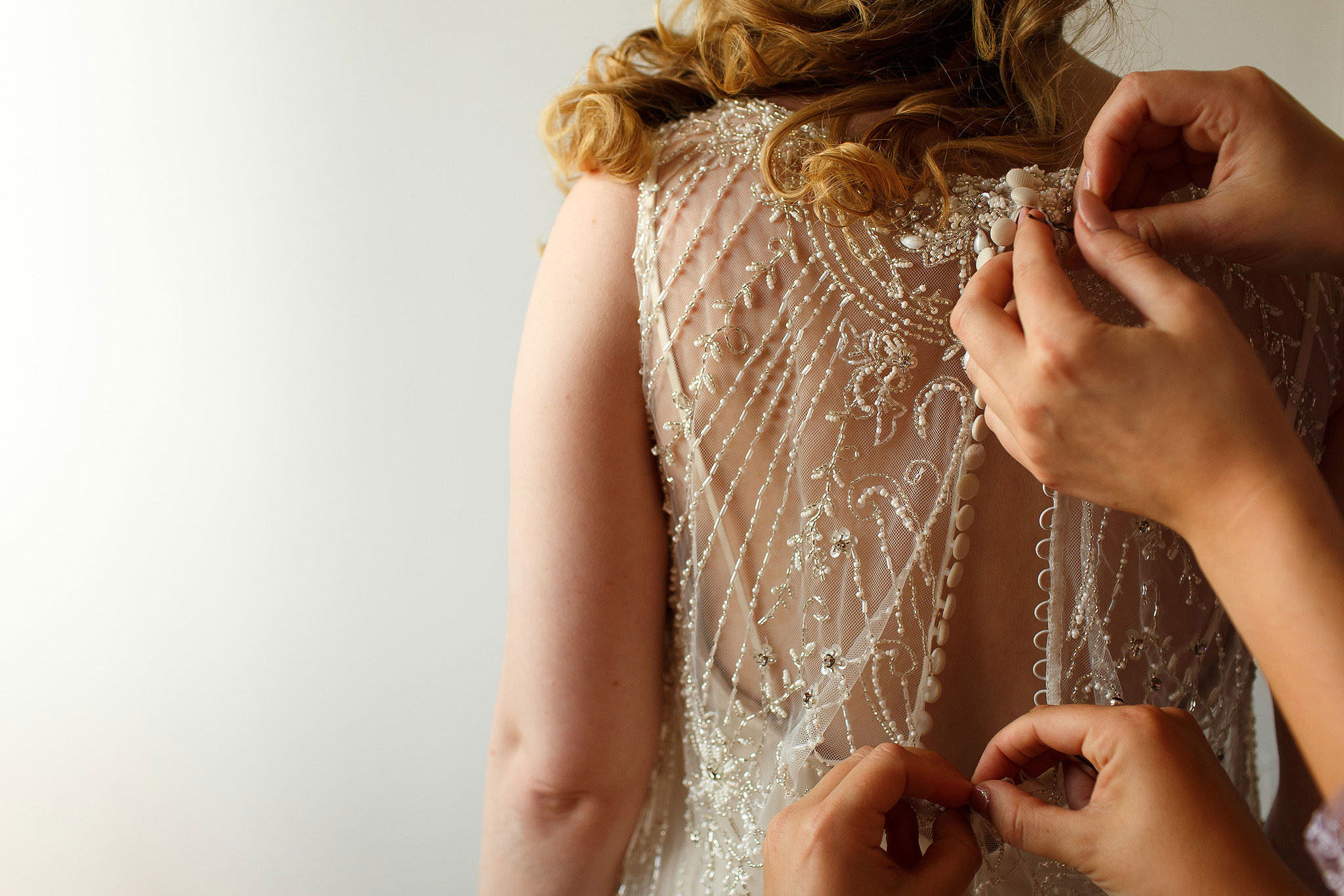 Detailed photograph of bride with blonde curls having her beaded wedding dress fastened by multiple hands - The Villa at Wrea Green Wedding Photography - Toni Darcy Photography