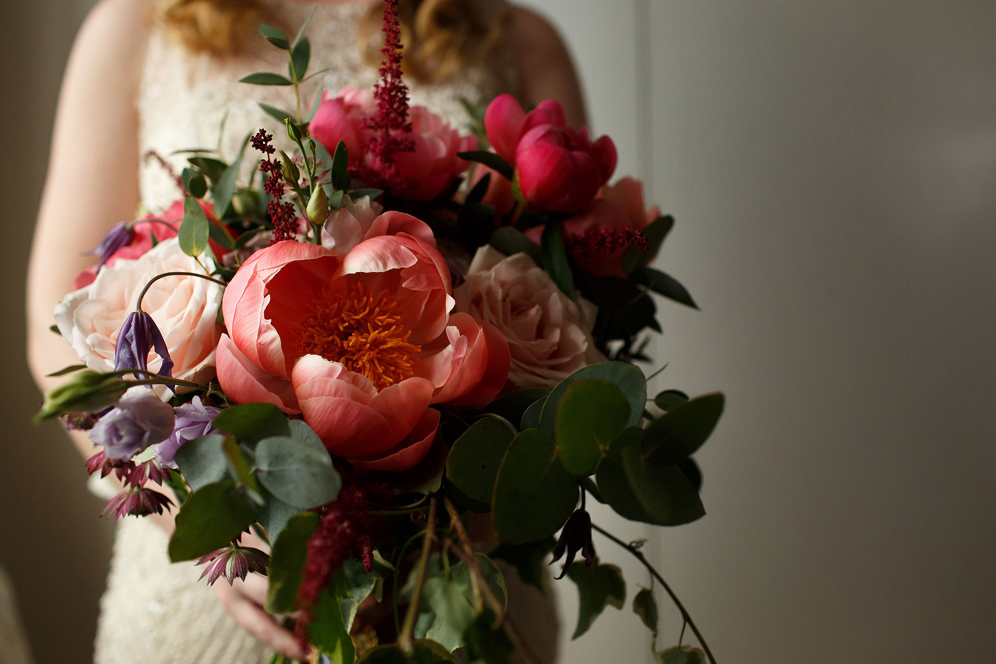 Gorgeous bridal bouquet with warm pink tones and unusual large flowers (peonies and poppies) being held by bride wearing beaded wedding dress - The Villa at Wrea Green Wedding Photography - Toni Darcy Photography