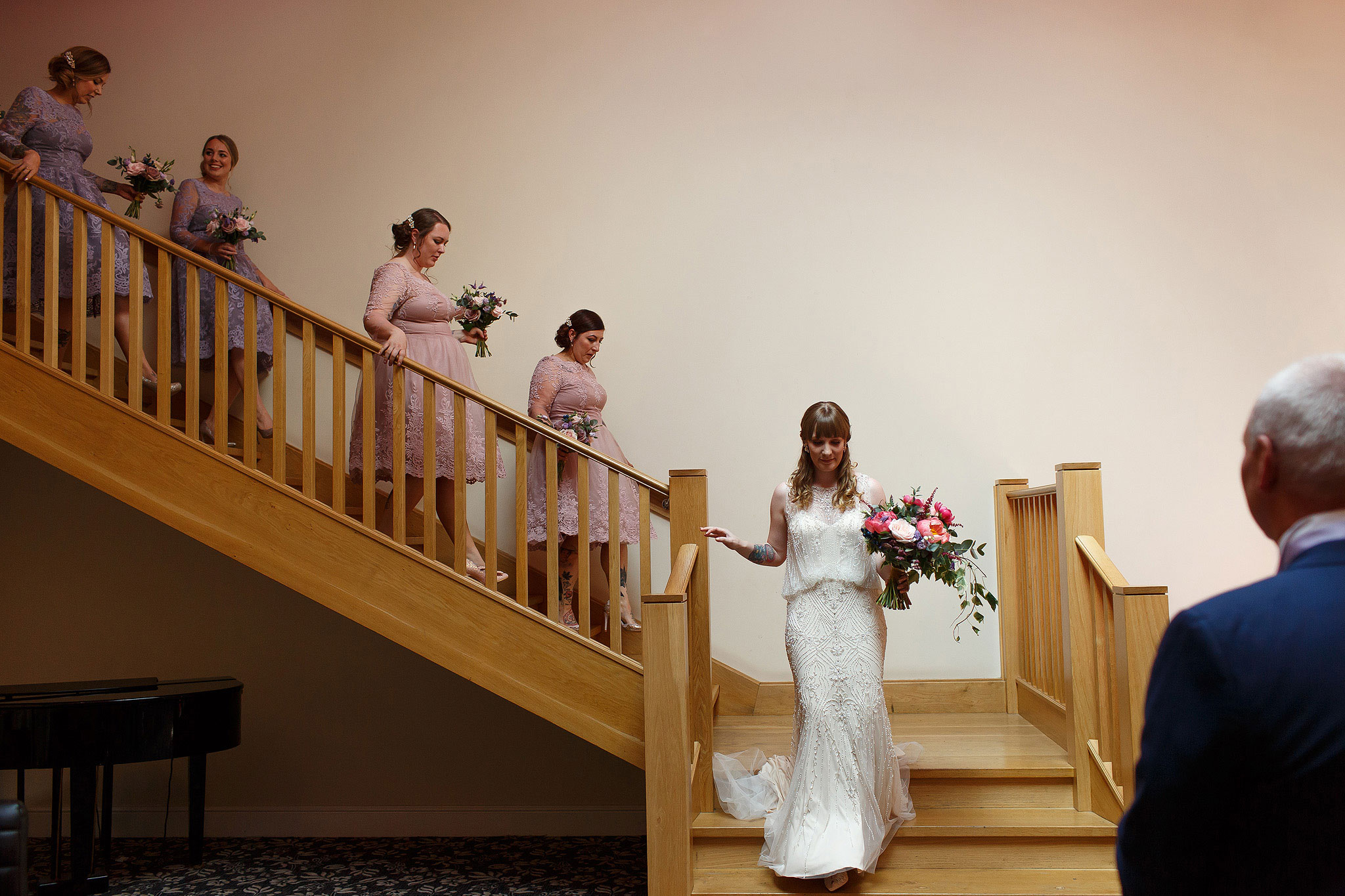 Bride and bridesmaids all walking down the staircase inside the Villa on the way to wedding ceremony - The Villa at Wrea Green Wedding Photography - Toni Darcy Photography