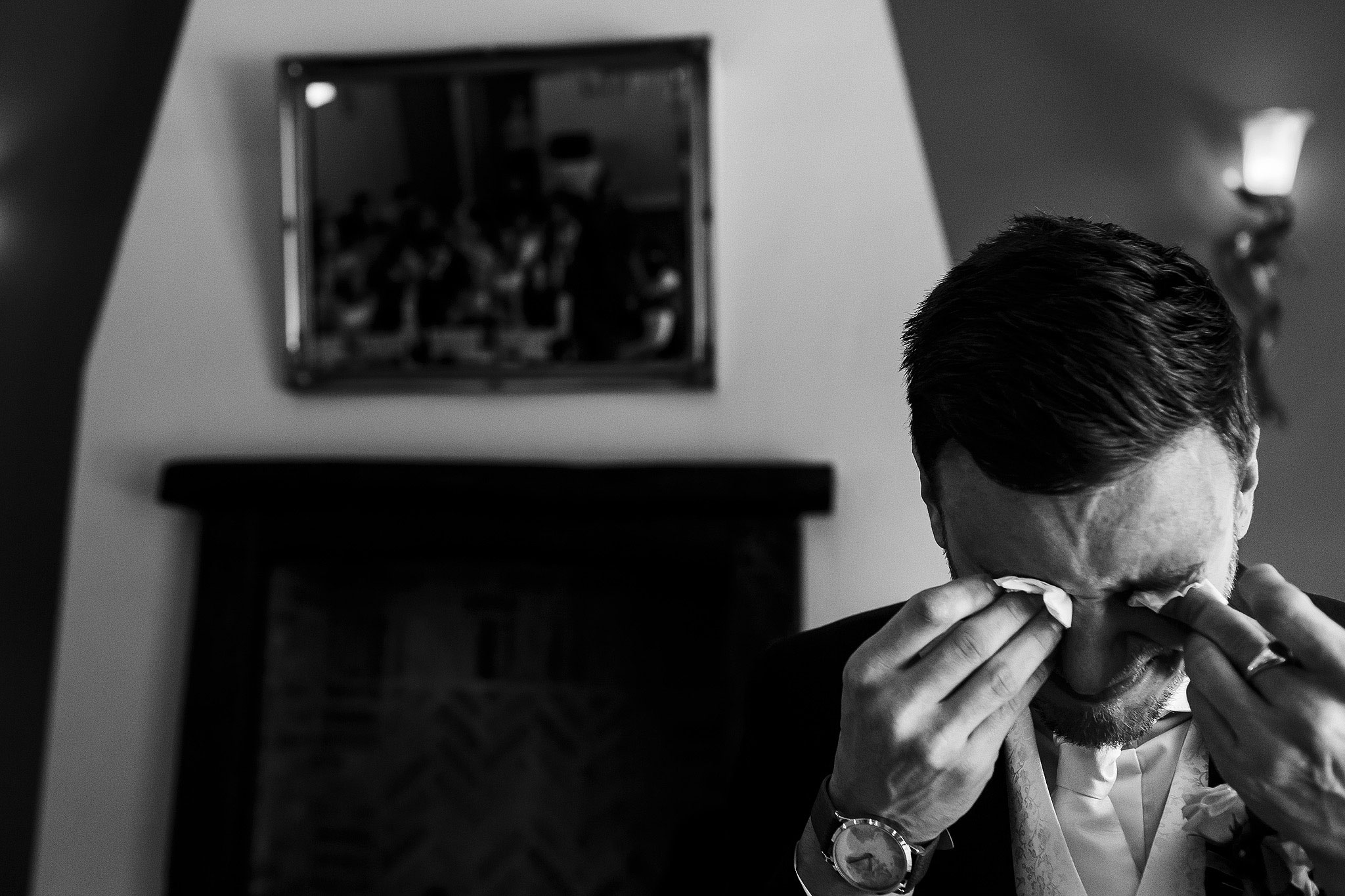 Black and white photograph of groom feeling emotional wiping eyes with tissue - The Villa at Wrea Green Wedding Photography - Toni Darcy Photography