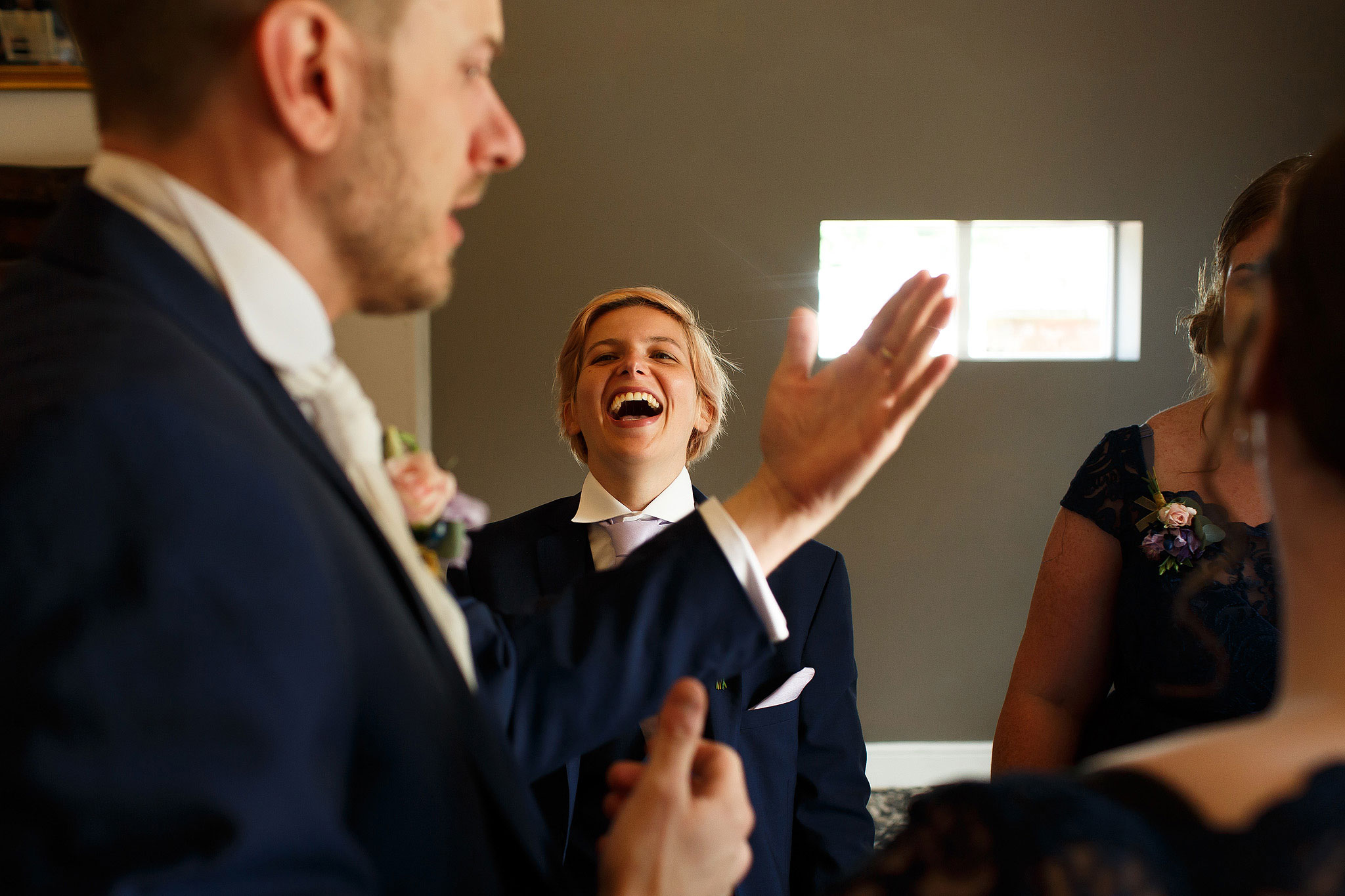 Grooms best woman laughing in navy suit - The Villa at Wrea Green Wedding Photography - Toni Darcy Photography