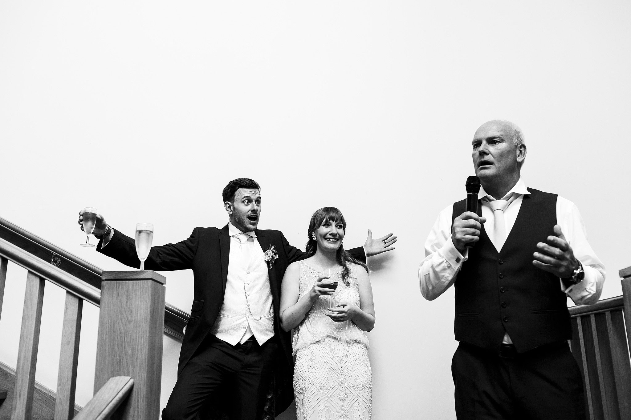 Black and white photograph of bride and groom watching the speeches - The Villa at Wrea Green Wedding Photography - Toni Darcy Photography