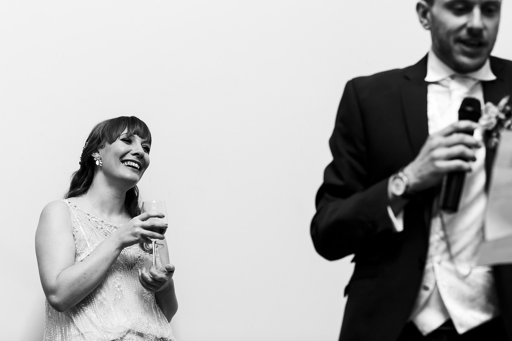Bride wearing beaded gown laughing towards husband during speeches - The Villa at Wrea Green Wedding Photography - Toni Darcy Photography