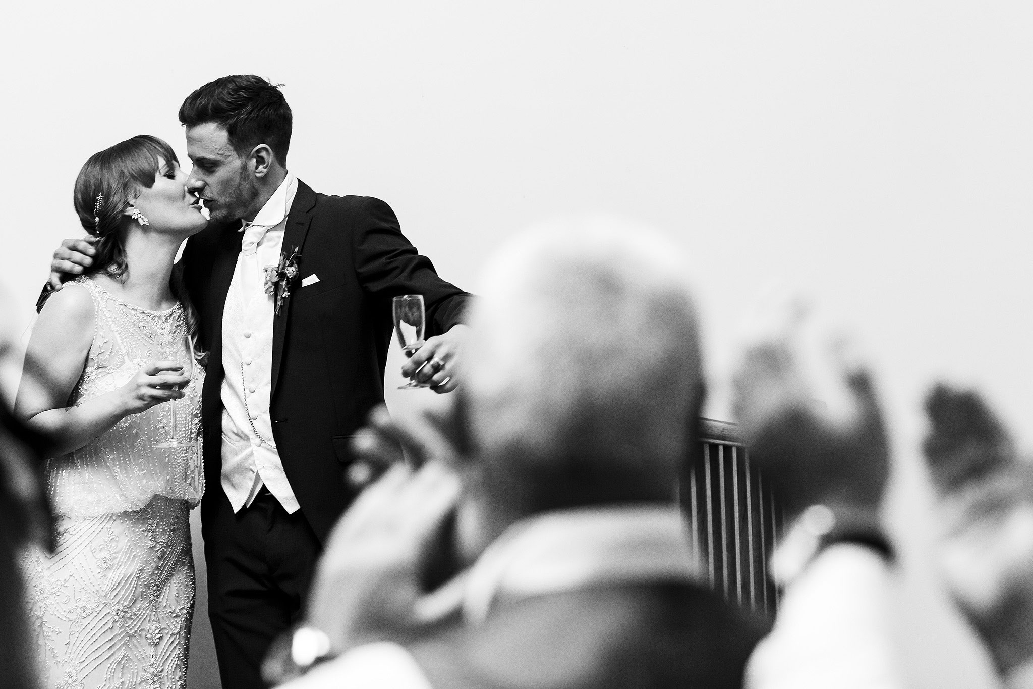 Bride and groom stealing a kiss during speeches - The Villa at Wrea Green Wedding Photography - Toni Darcy Photography