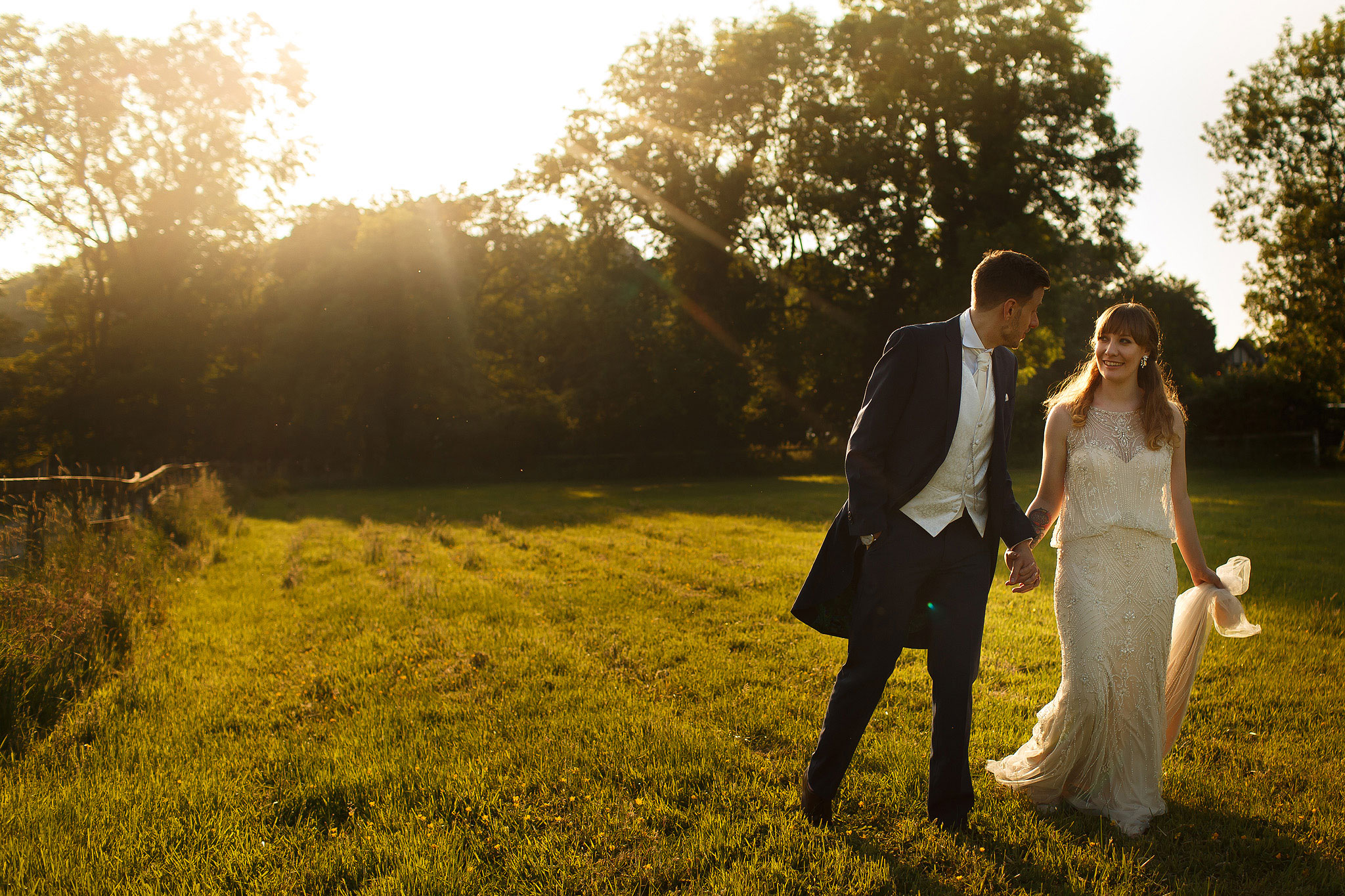 Bride and groom wedding day portraits walking through the fields in gorgeous sunlight in the gardens - The Villa at Wrea Green Wedding Photography - Toni Darcy Photography