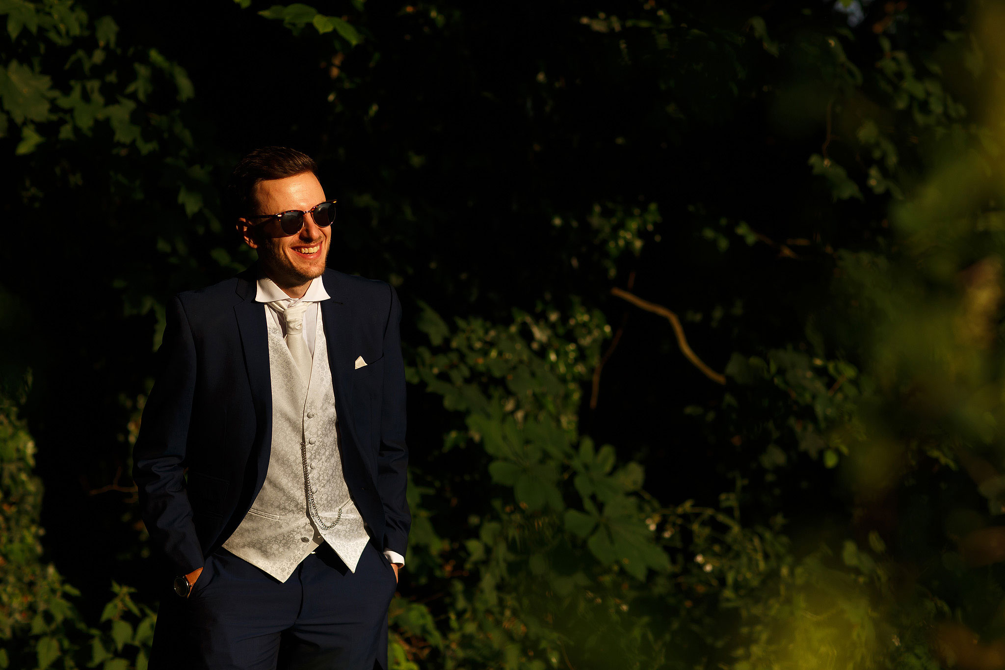 Groom wearing navy suit and cream waist coat and sunglasses during couple wedding day portraits - The Villa at Wrea Green Wedding Photography - Toni Darcy Photography