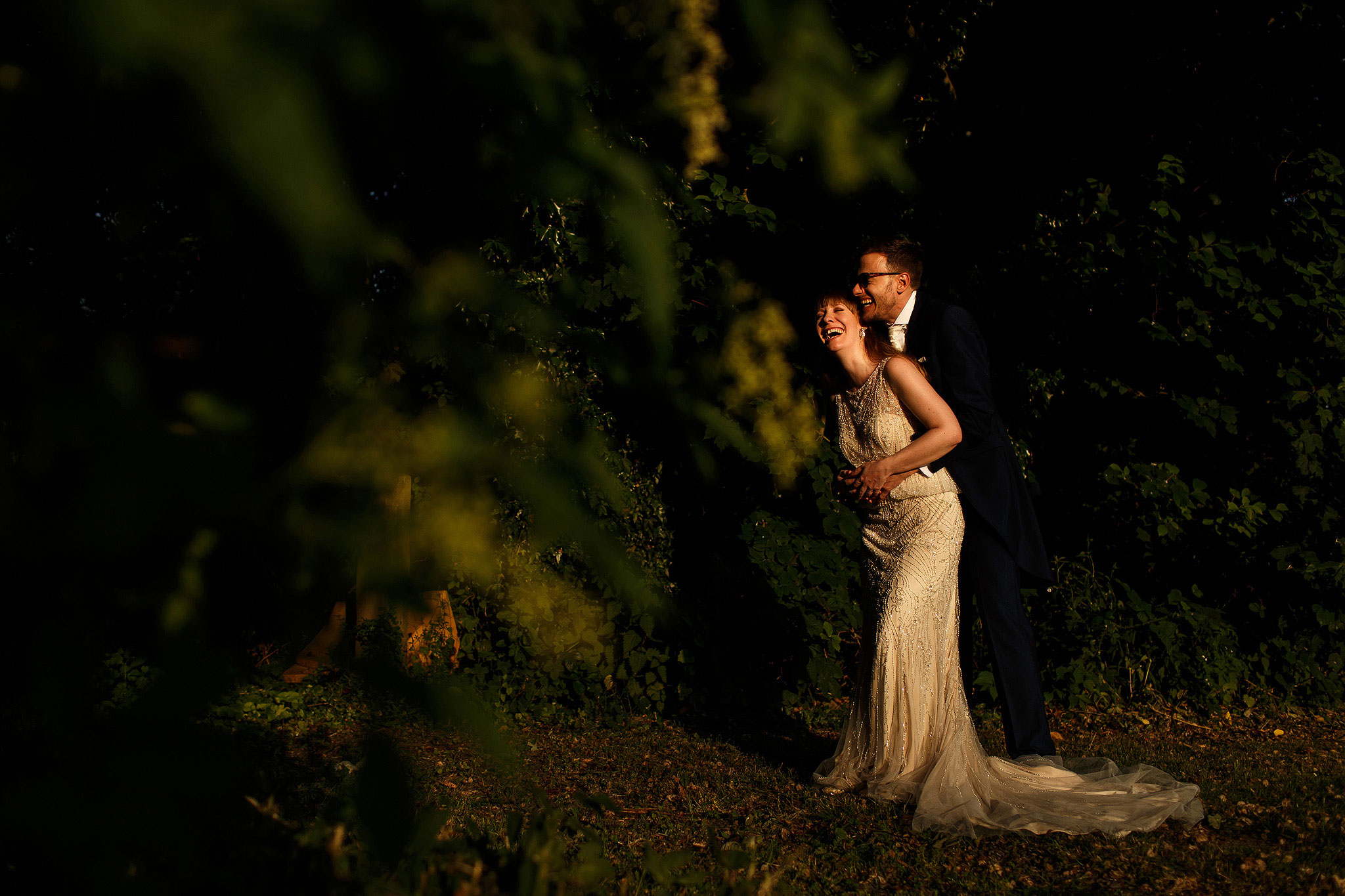 Bride wearing beautiful beaded floor length wedding gown laughing in the arms of her groom in beautiful sunlight during the wedding day portraits - The Villa at Wrea Green Wedding Photography - Toni Darcy Photography