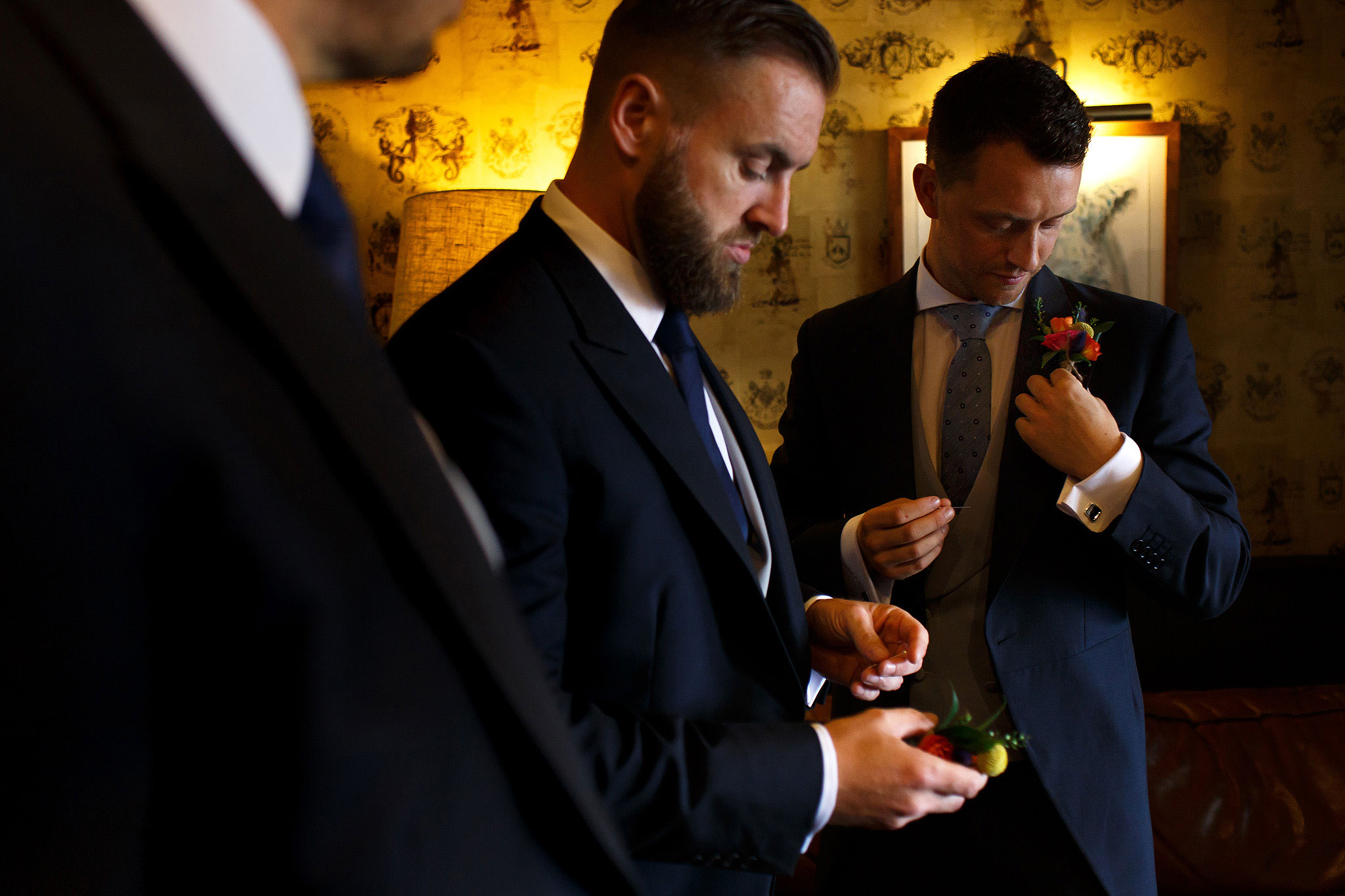Groom and groomsmen fixing on their button hole flowers