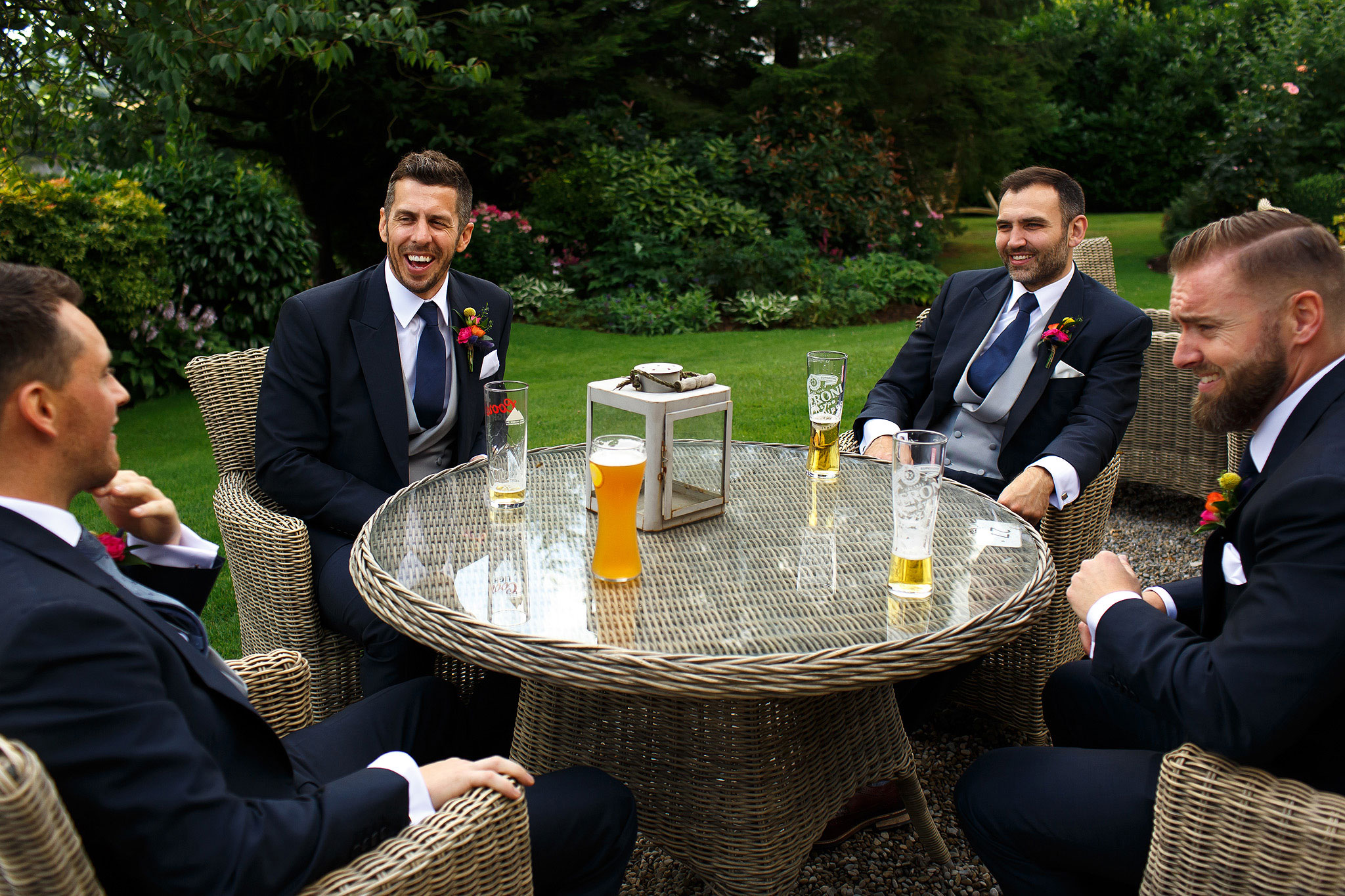Groom and groomsmen drinking a beer in the garden at Shireburn Arms