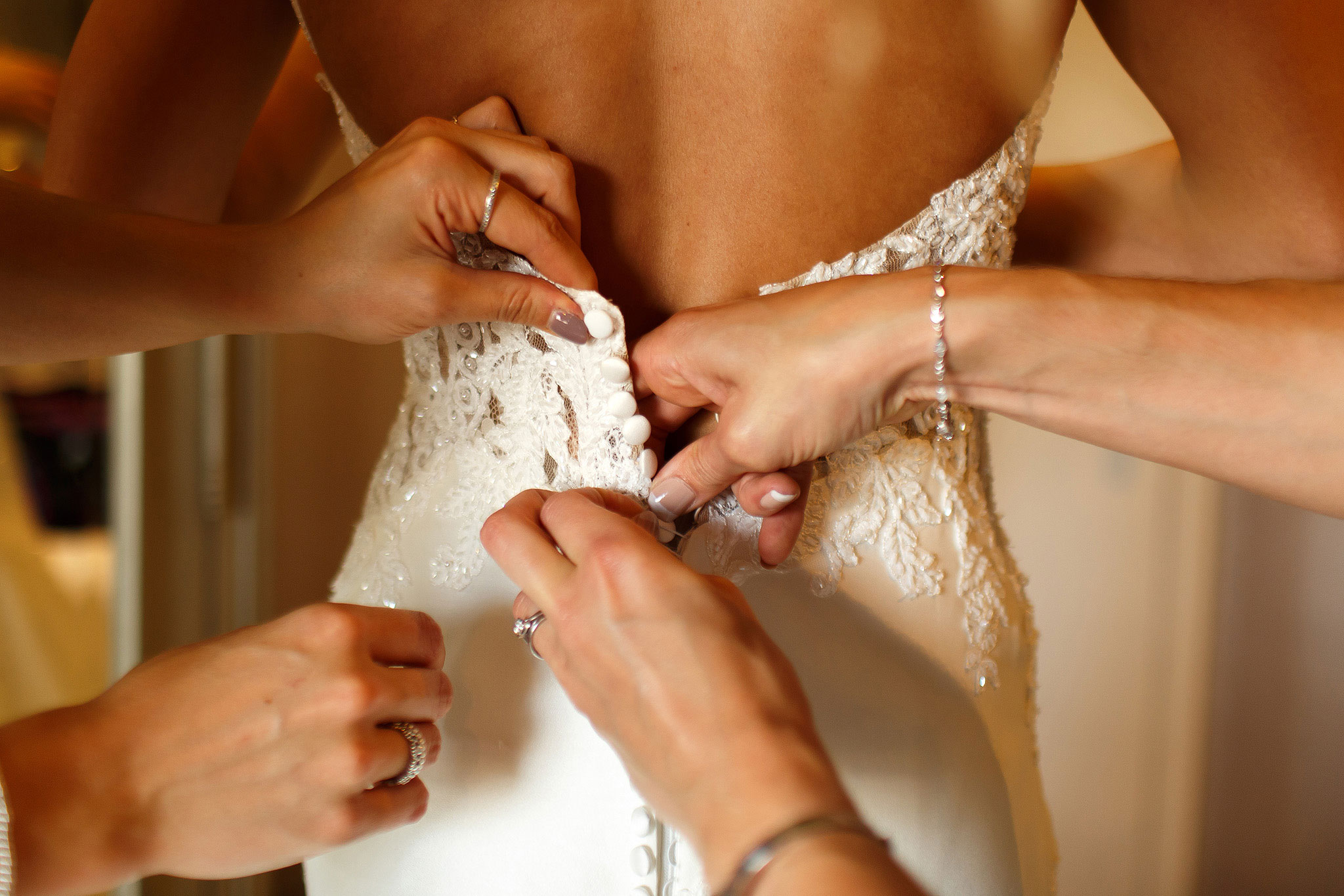 Pairs of hands tying the brides wedding dress