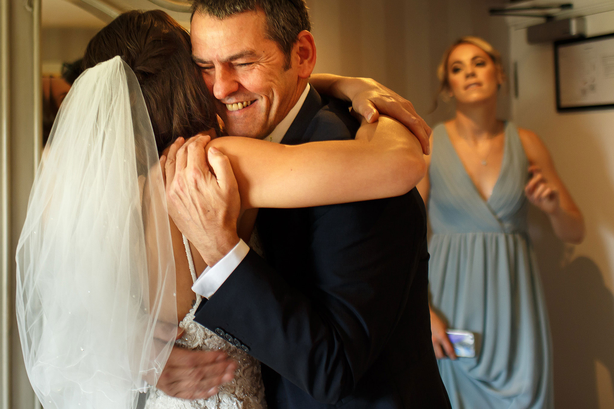 Father of the bride hugging bride as he sees her in her dress for the first time