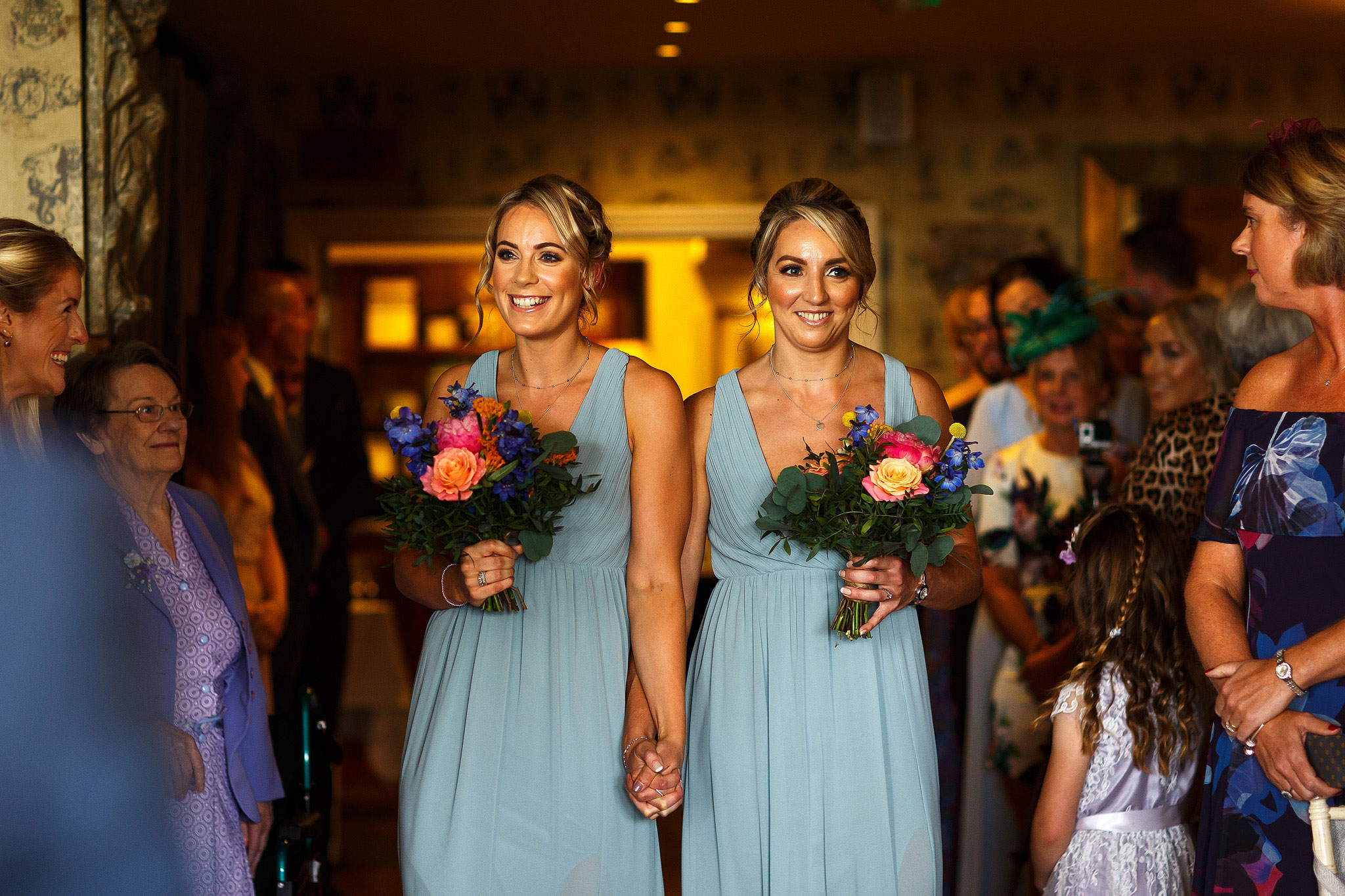 Bridesmaids with colourful flowers walking down the aisle wearing long pale blue dresses
