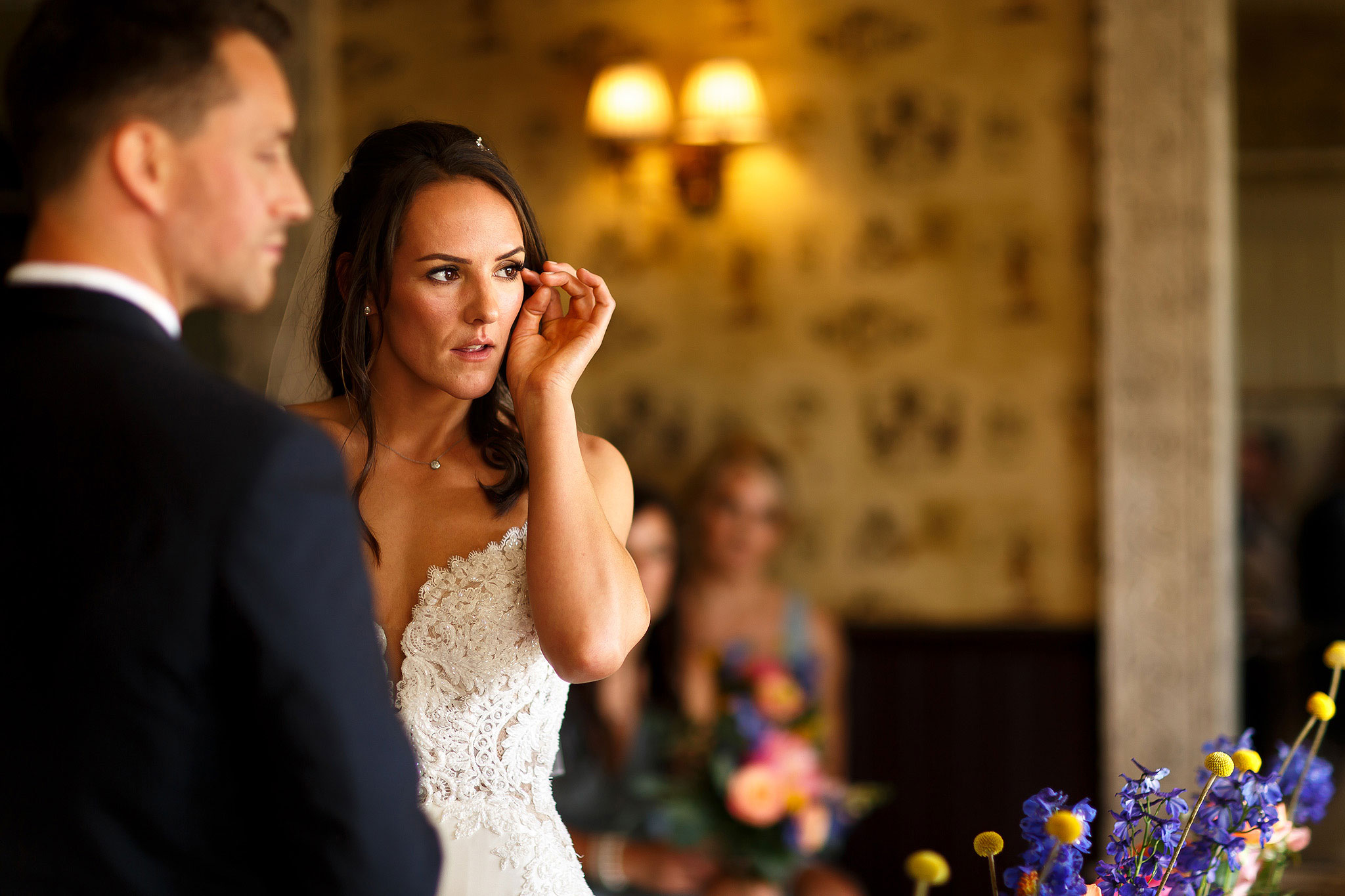 Bride delicately wiping tears during wedding ceremony at the Shireburn Arms