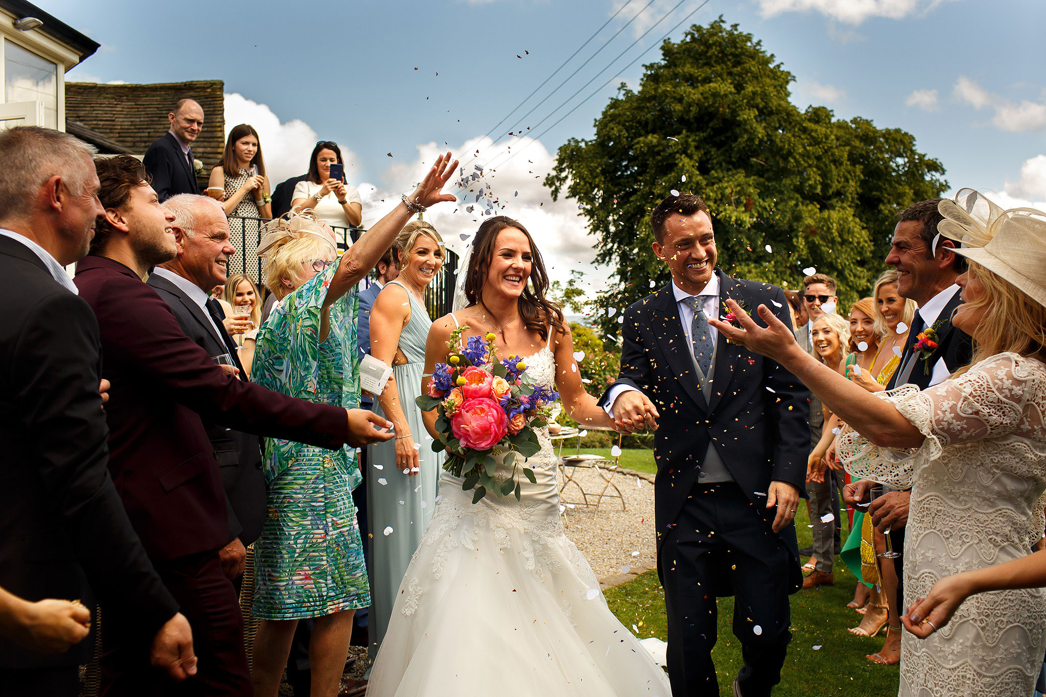 Bride and groom walking through confetti throwing in the garden at Shireburn Arms