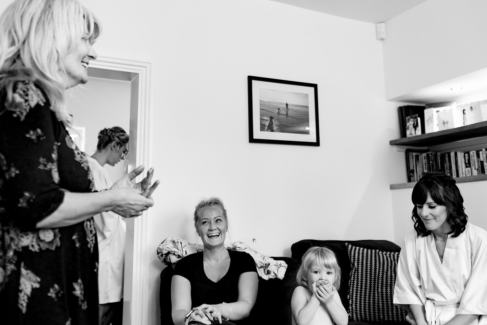 Documentary scene setting image of bridal party sat on the sofa laughing