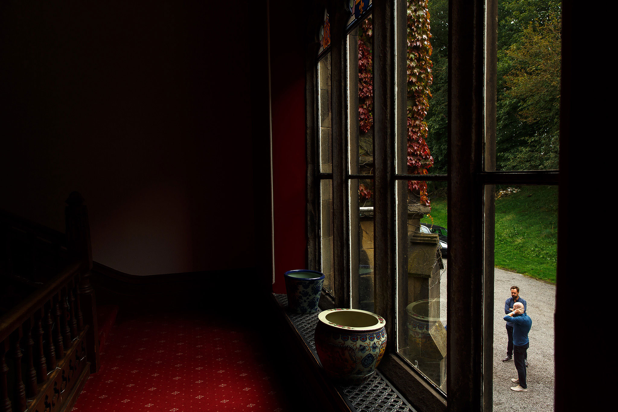 Groom nervously waiting outside, view from window inside | Hargate Hall Wedding Photography