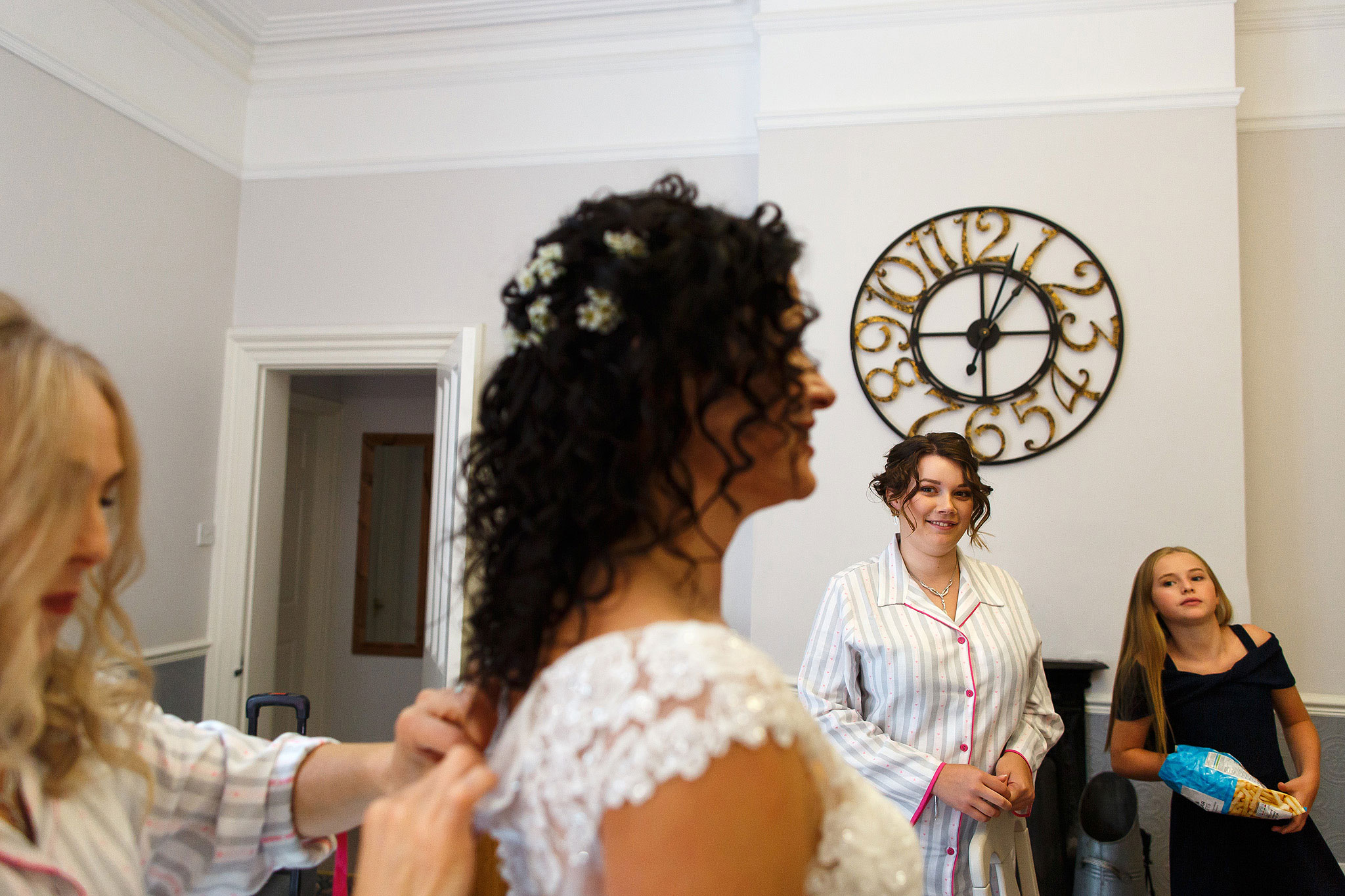 Bridesmaids looking towards bride as she has her dress fastened with clock on the wall showing time | Hargate Hall Wedding Photography