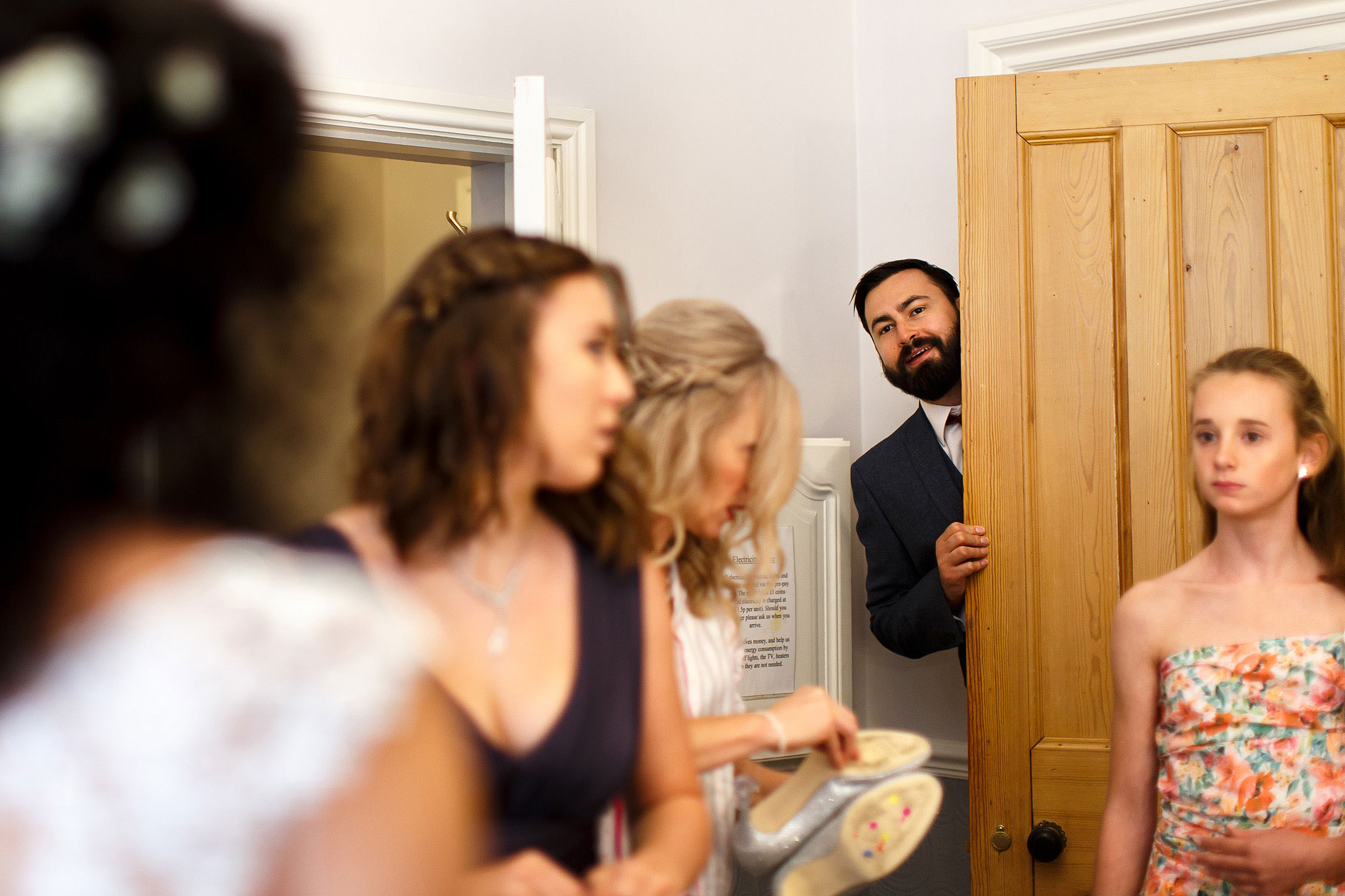 Groomsmen popping his head around the door as he enters the room where all the bridesmaids and brides are waiting to leave for the ceremony | Hargate Hall Wedding Photography
