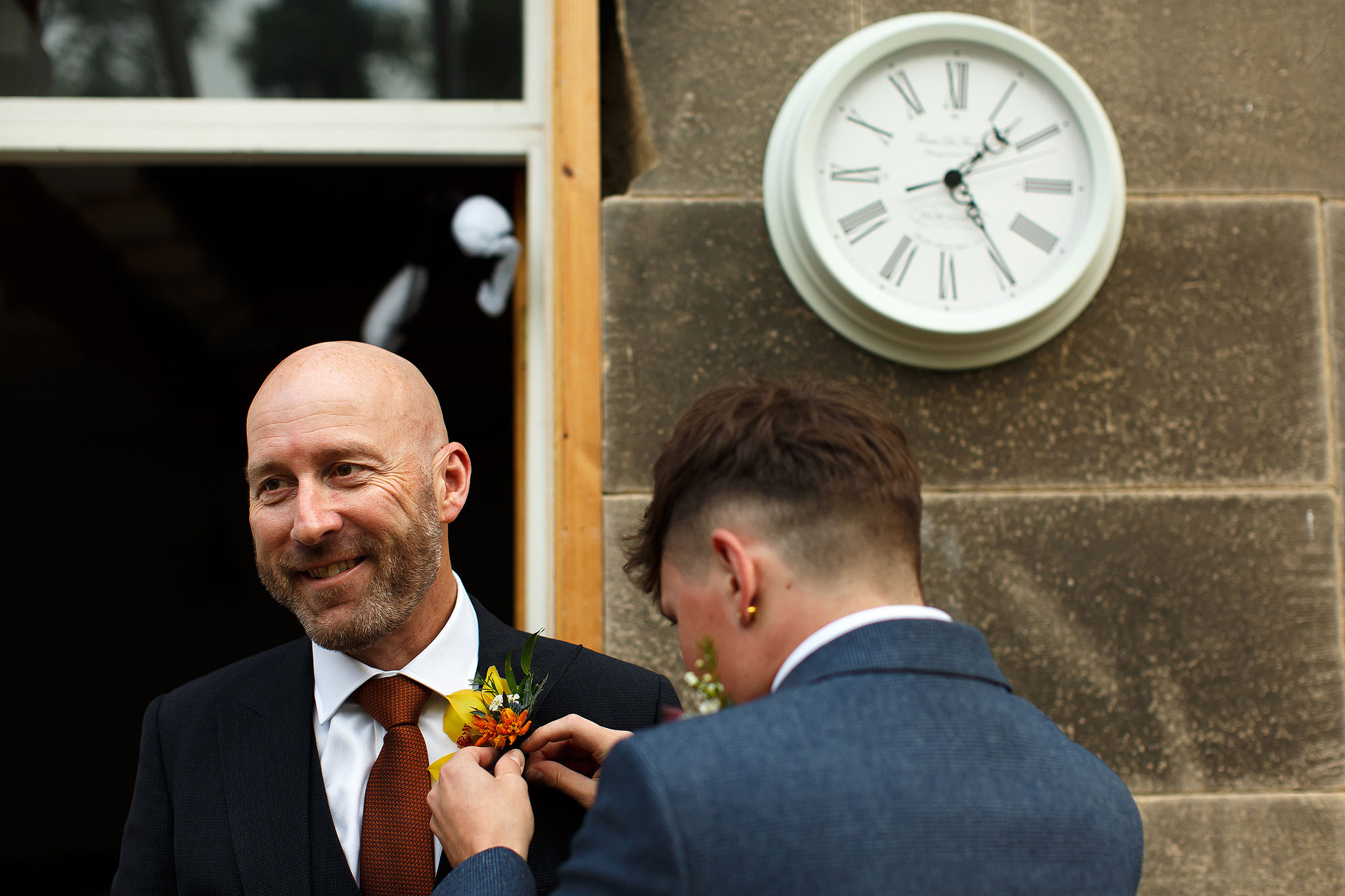 Groom having button hole pinned on with clock in background | Hargate Hall Wedding Photography