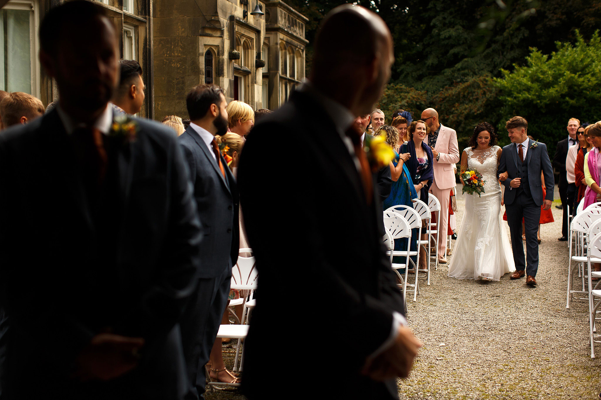 Bride walking down the aisle of outdoor wedding ceremony | Hargate Hall Wedding Photography