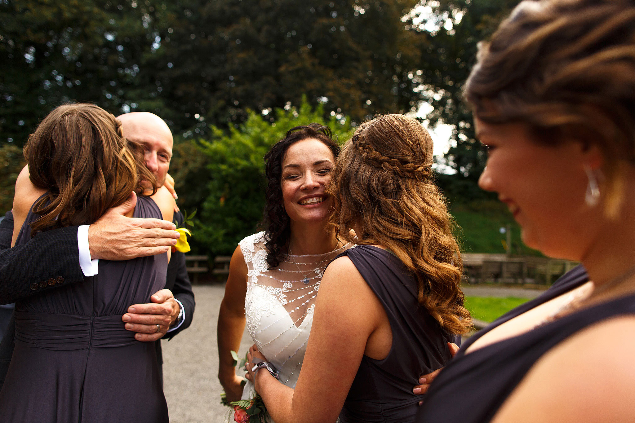 Bride and groom hugging bridal party during drinks reception outdoors | Hargate Hall Wedding Photography