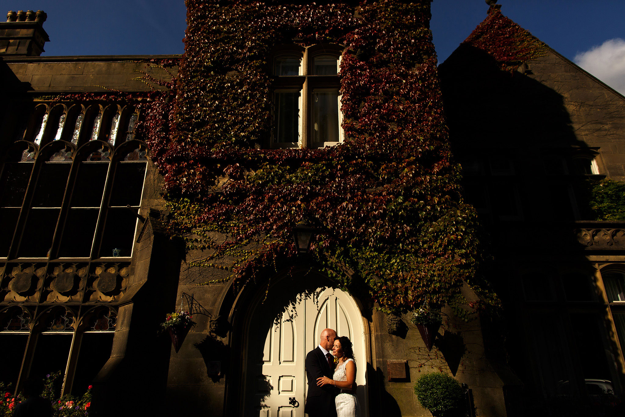 Bride and groom stood in the white door way at the front of Hargate Hall | Hargate Hall Wedding Photography