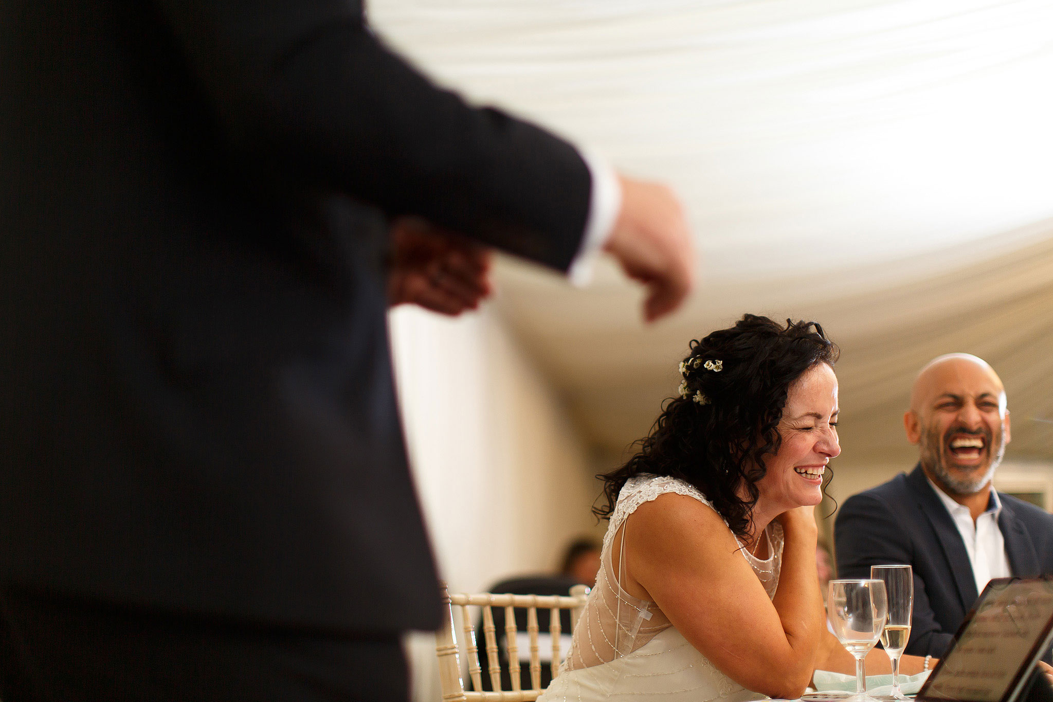 Bride laughing inside marquee during speeches | Hargate Hall Wedding Photography