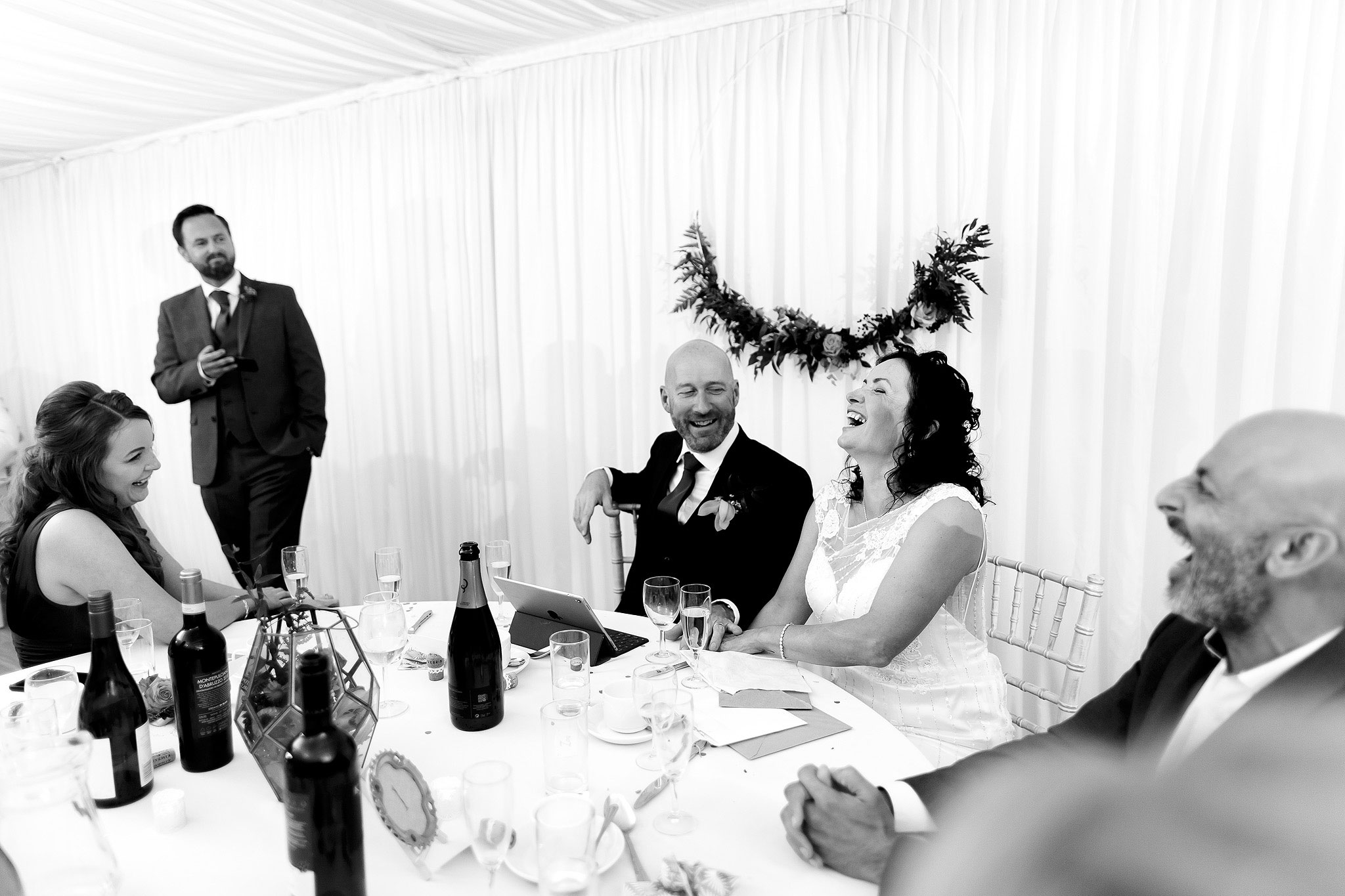 Bride and groom top table during speeches inside marquee | Hargate Hall Wedding Photography