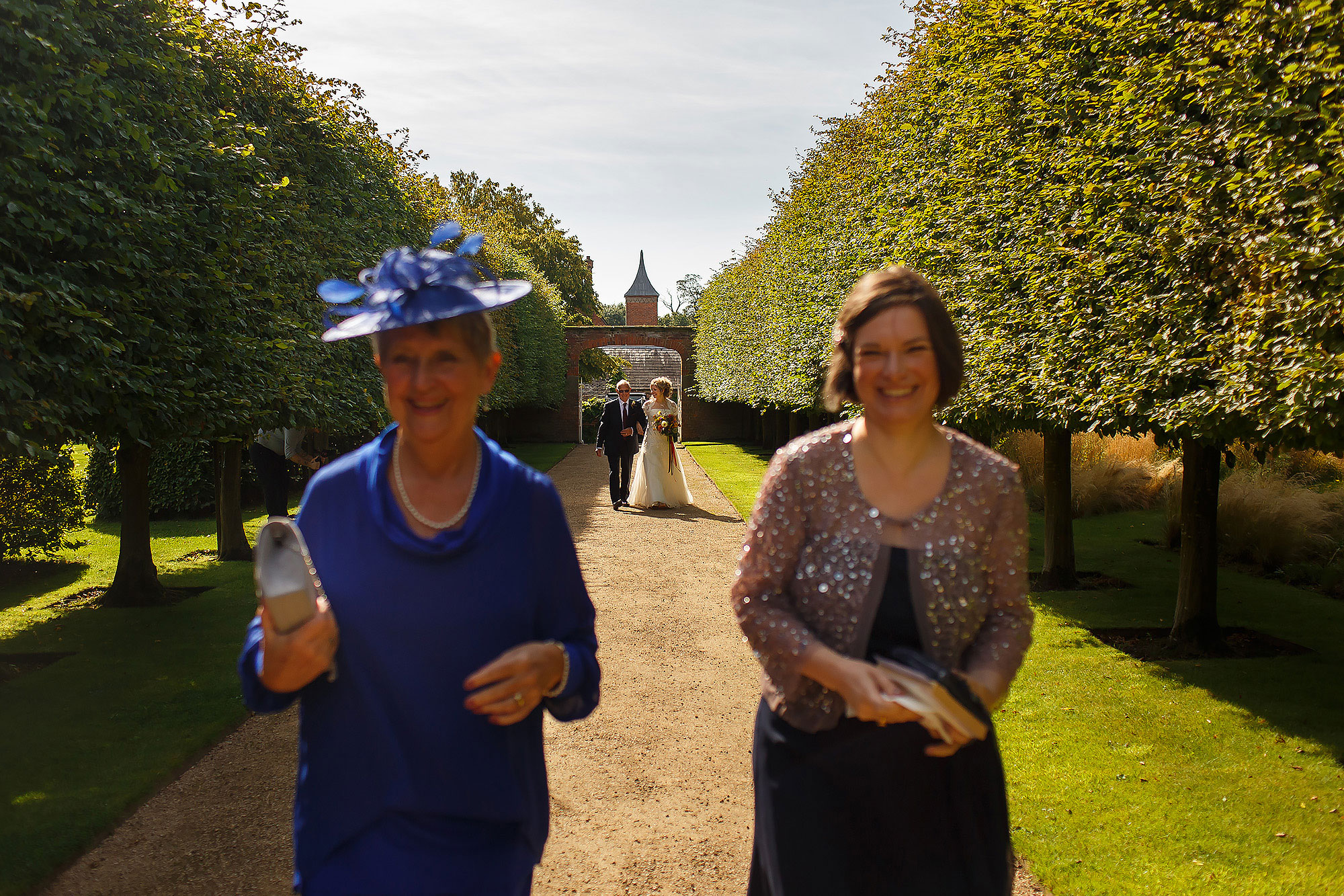 Bride walking through the gardens of Combermere Abbey to Orangerie for wedding