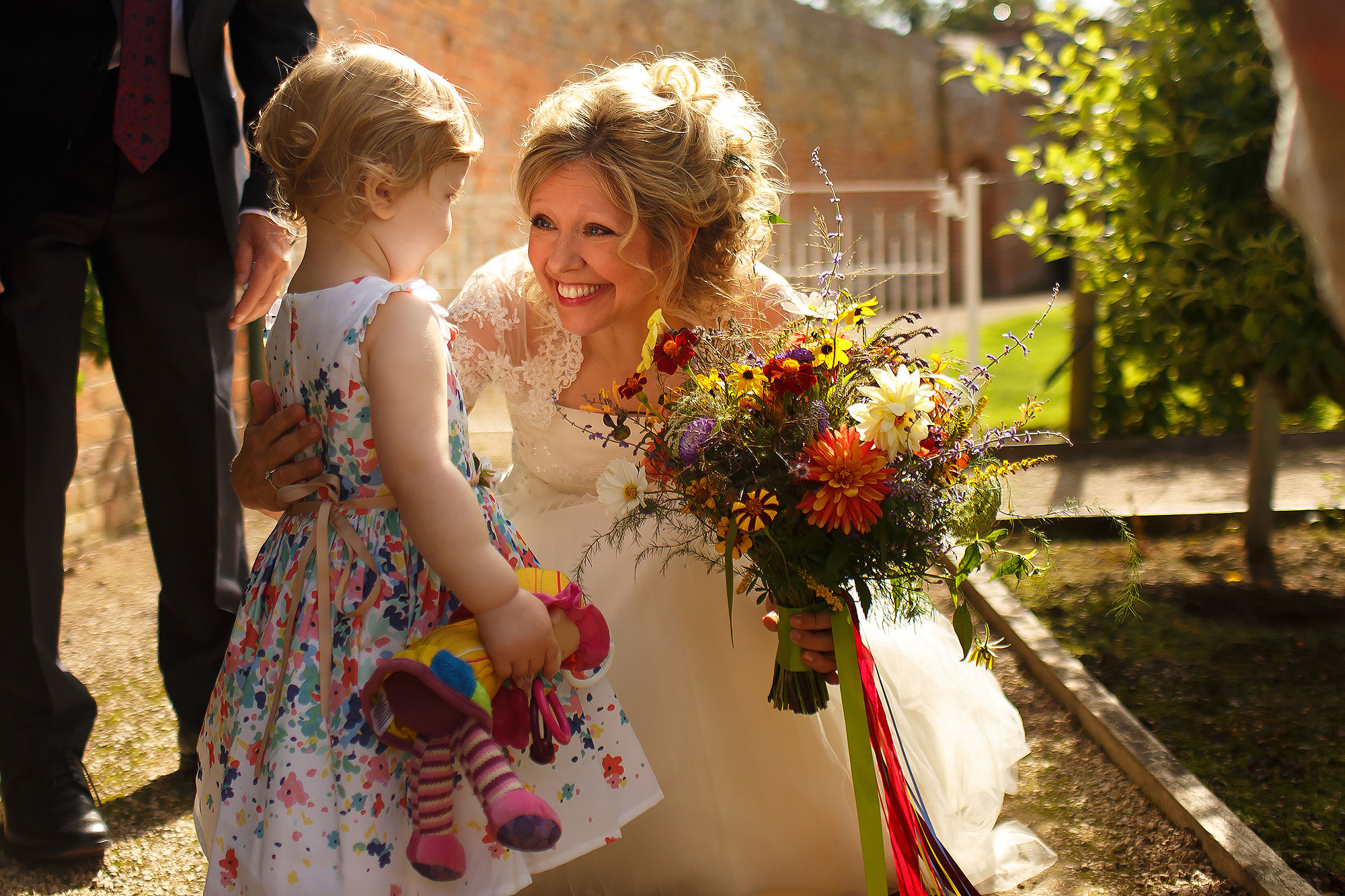Bride with blonde hair and colourful flowers hugging flower girl