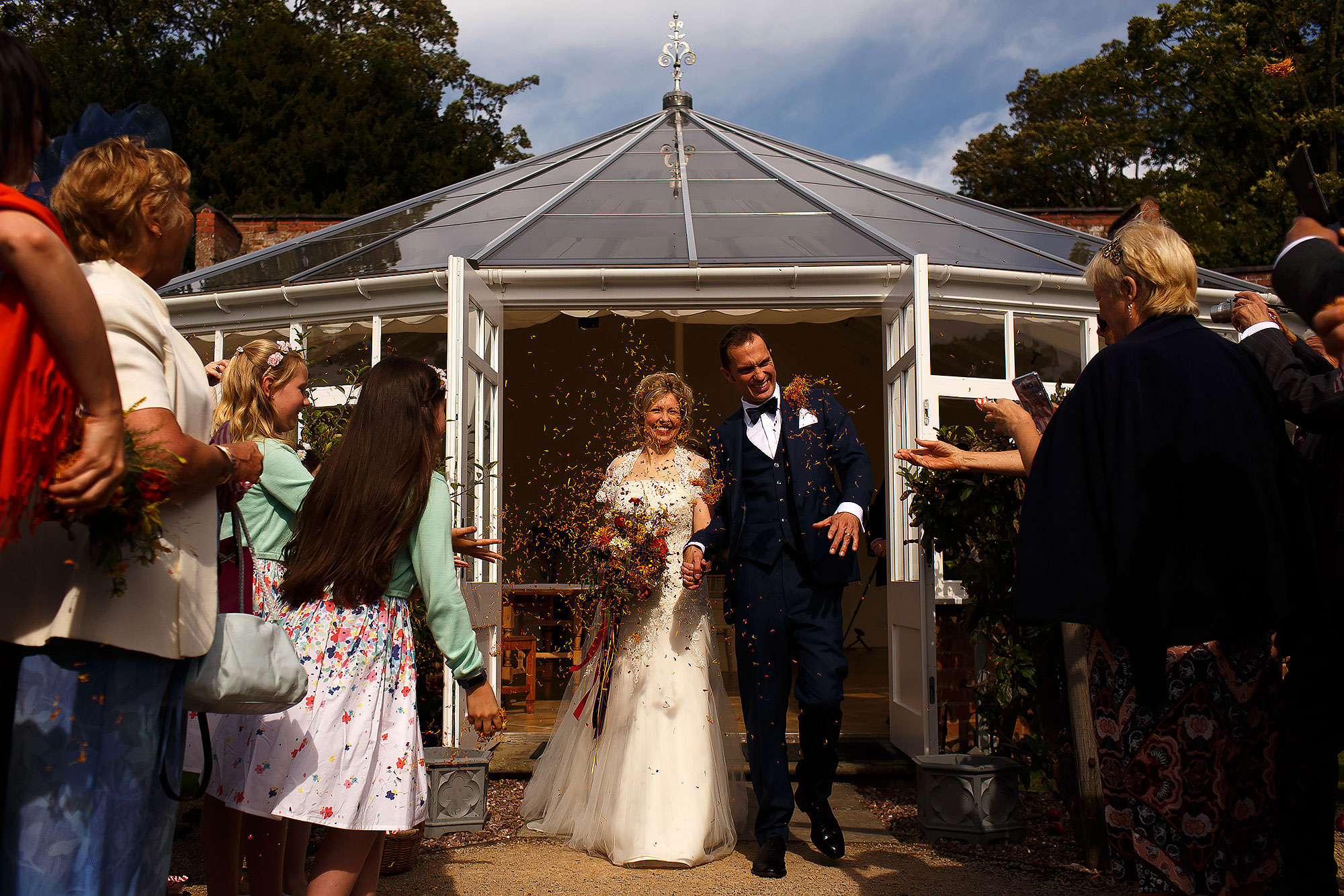 Bride and groom walking out of the french doors of the orangerie at Combermere Abbey Wedding into the confetti